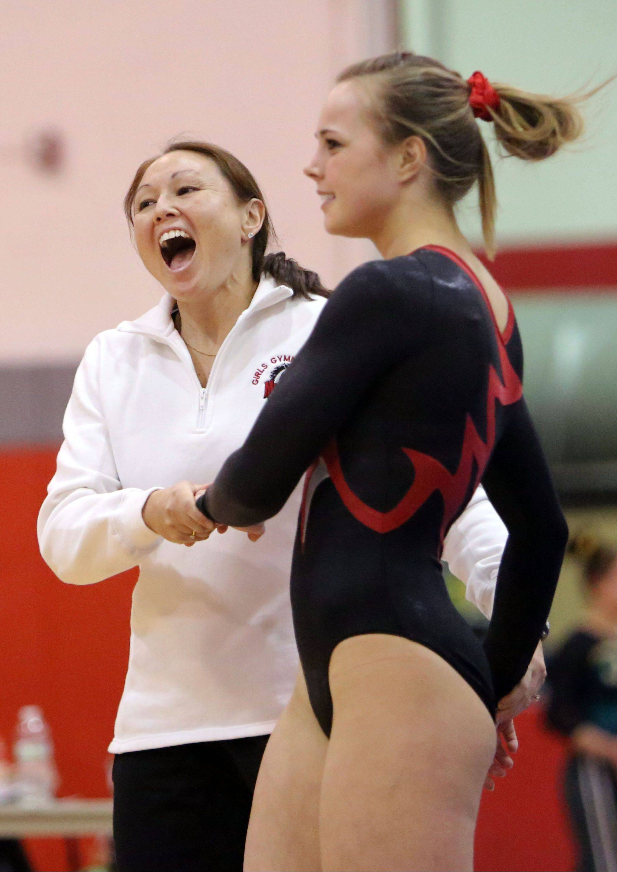 Mundelein coach Nancy Toland, left, celebrates with McKenzie Kehr after her balance beam routine during regional gymnastics action Monday at Mundelein.