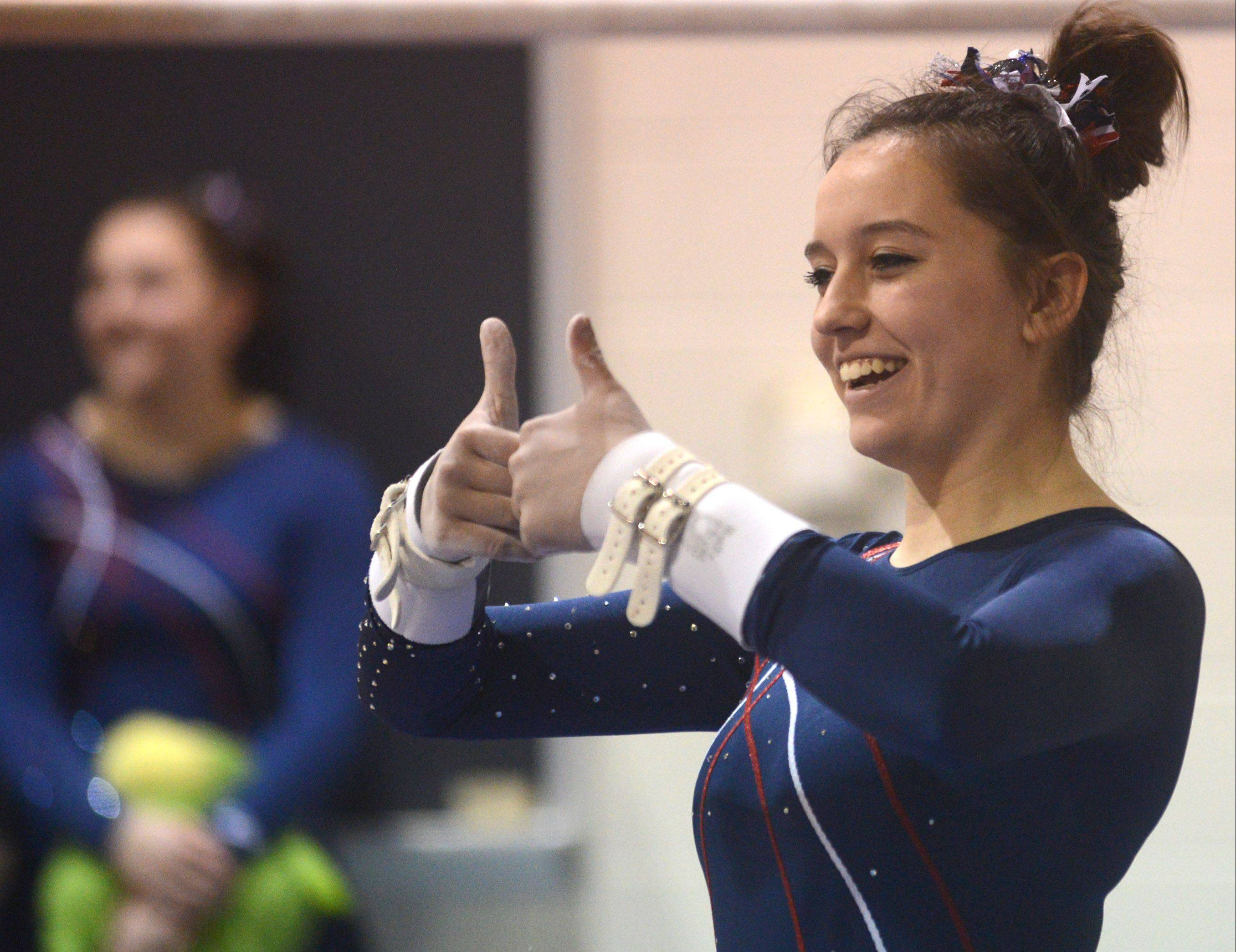 Conant's Ali Kelly acknowledges fans in the stands before her uneven parallel bars routine during Monday's regional hosted by Barrington.