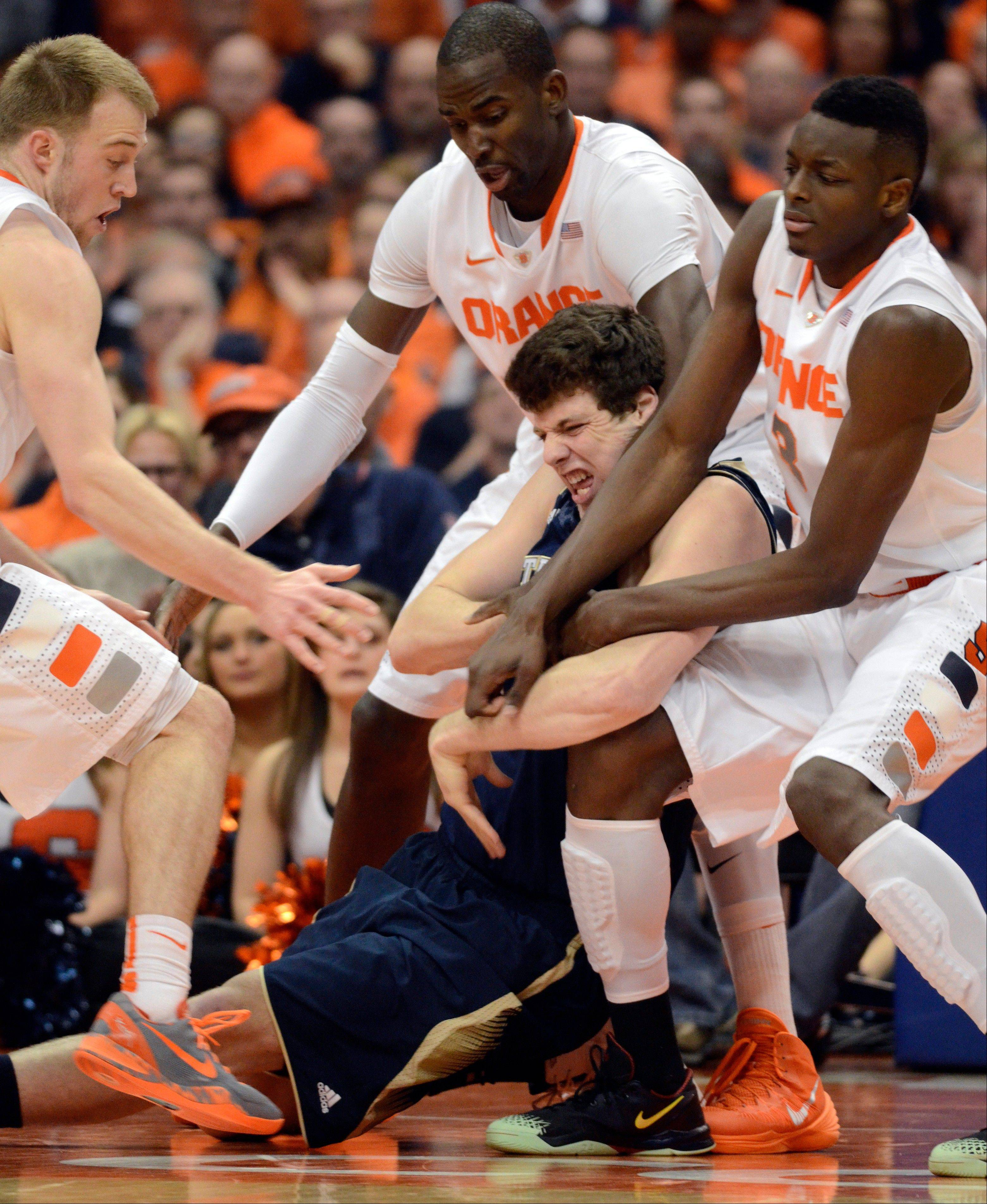 Notre Dame's Tom Knight battles with Syracuse's, from left, Trevor Cooney, Baye Moussa Kieta and Jerami Grant for a loose ball during the second half of an NCAA college basketball game in Syracuse, N.Y., Monday, Feb. 3, 2014. Syracuse won 61-55.