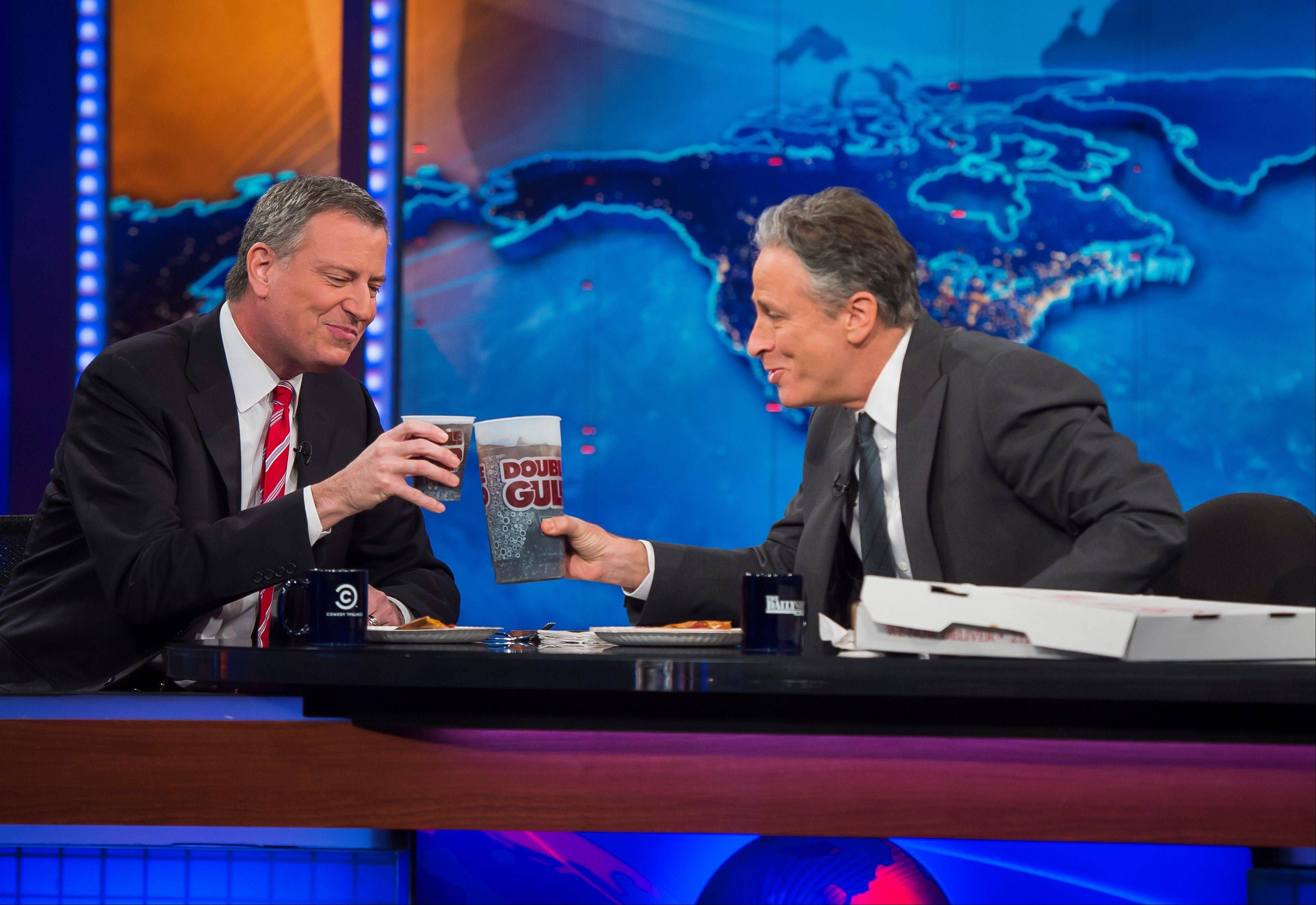 "New York Mayor Bill de Blasio, left, shares pizza and soda with host Jon Stewart on Comedy Central's ""The Daily Show"" on Monday in New York."
