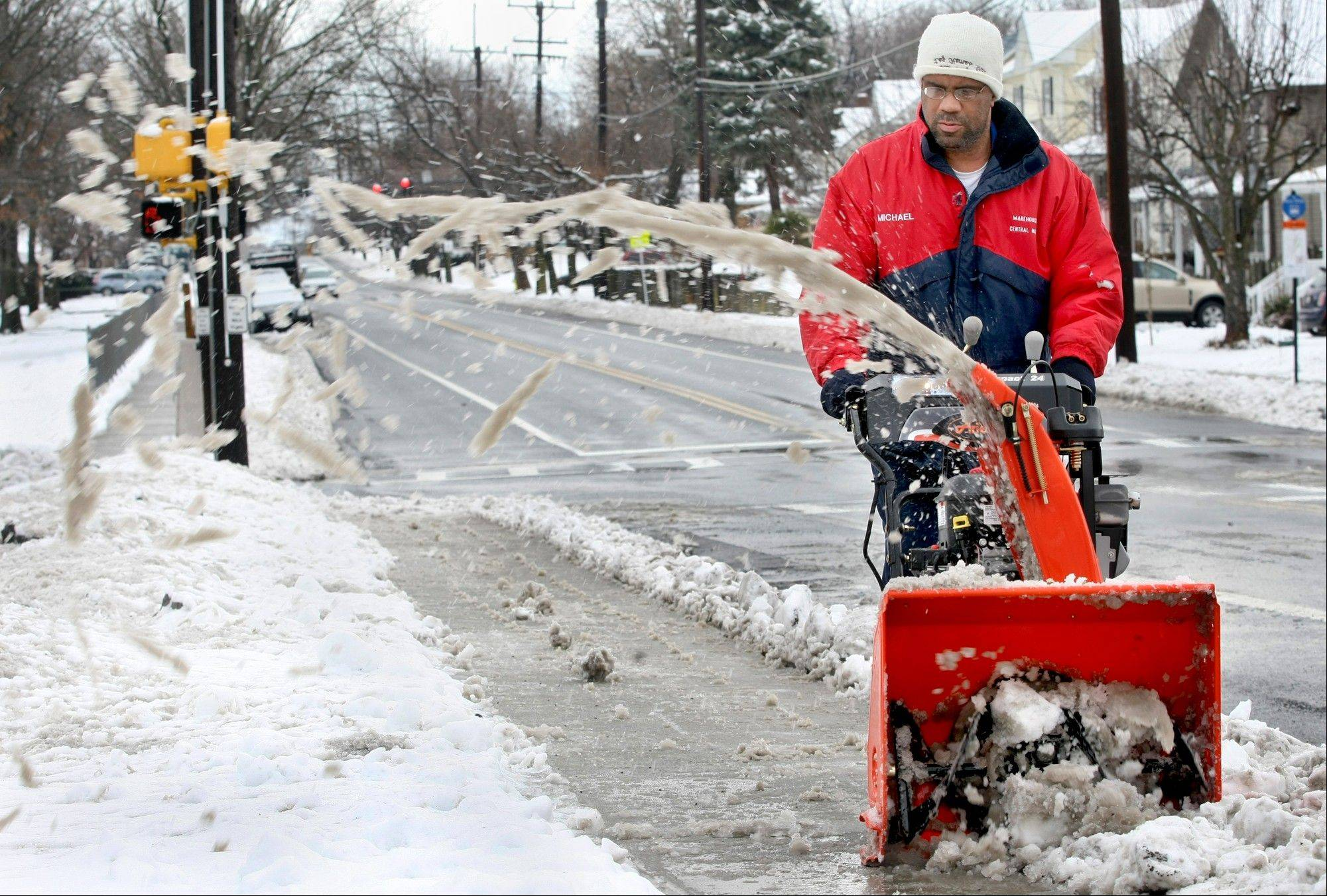 Michael Page uses a snowblower to remove several inches of heavy, wet snow from the sidewalk in front of his Winchester, Va., home on Monday, Feb. 3, 2013. Winter storm Maximus swept through the area dumping snow in the area closing schools and government offices.