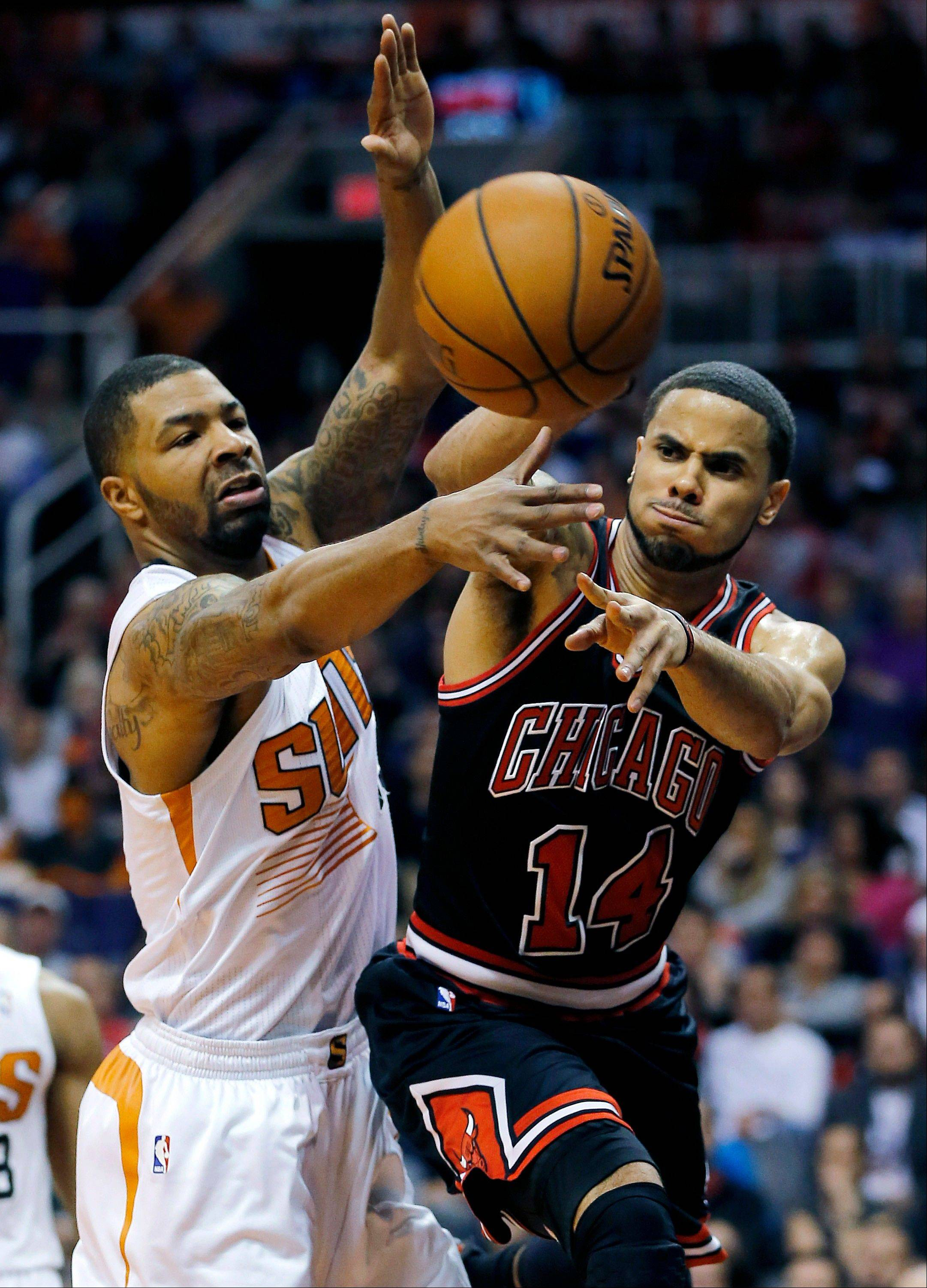 Bulls guard D.J. Augustin passes around the Suns� Markieff Morris during the first half Tuesday night. Augustin finished with 18 points in the Bulls� victory.