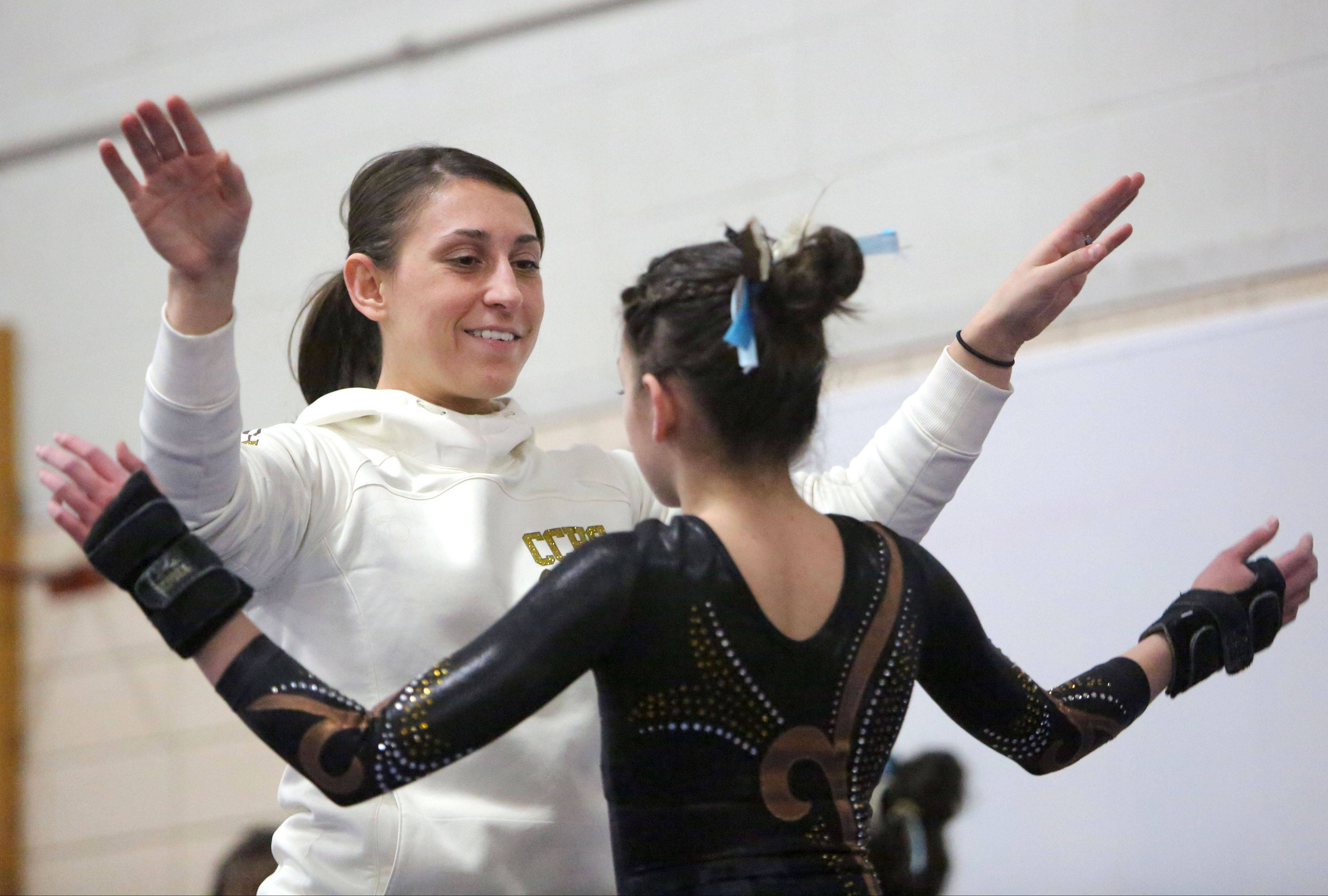 Carmel assistant coach Nicole Stroup celebrates with Alyssa Legerreta after a vault during regional action Tuesday at Deerfield.