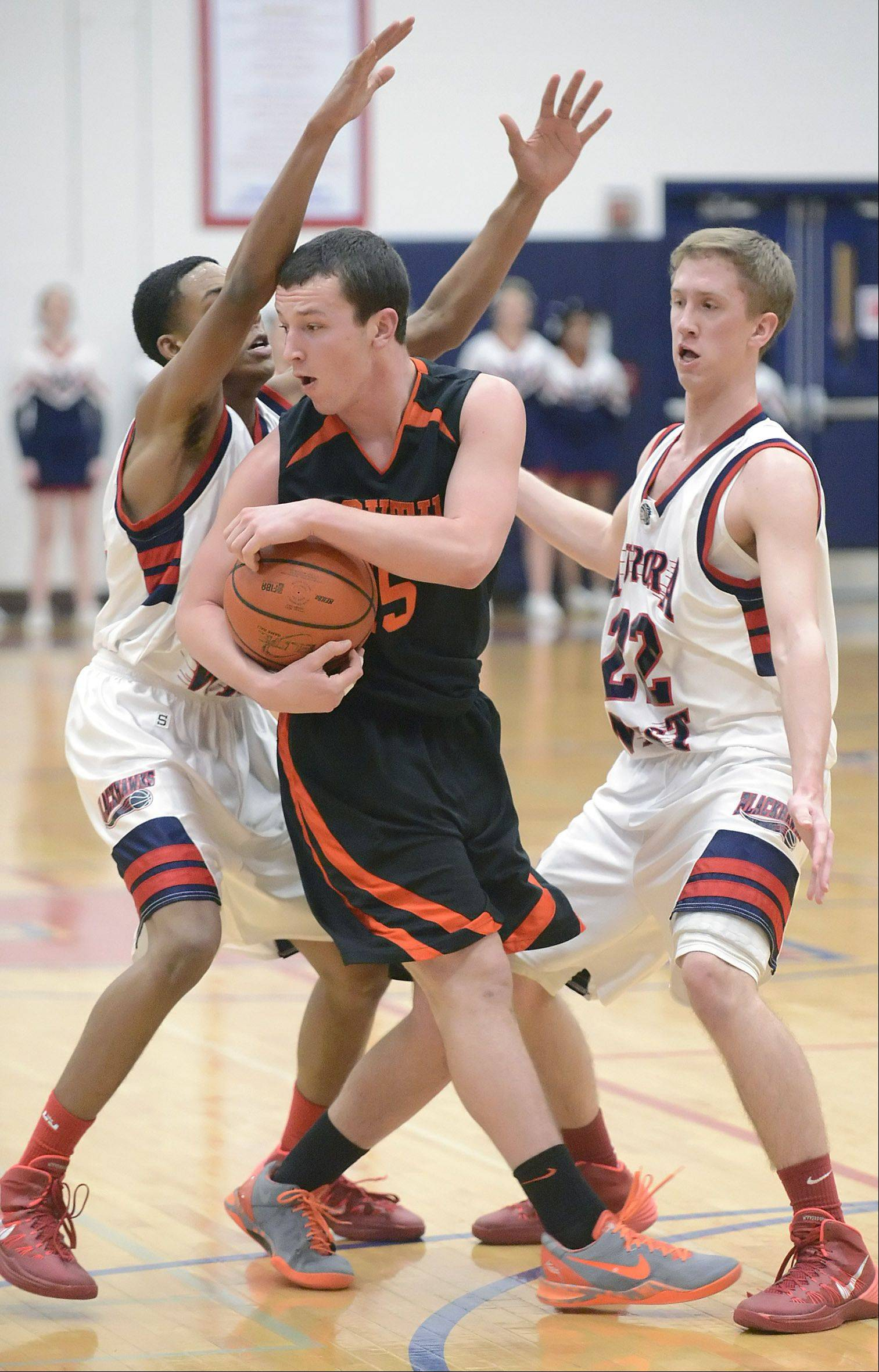 Wheaton Warrenville South�s Joe Metzger is swarmed by West Aurora�s Antwan Ahamd, left, and Tommy Koth, right, in the third quarter on Tuesday, February 4.