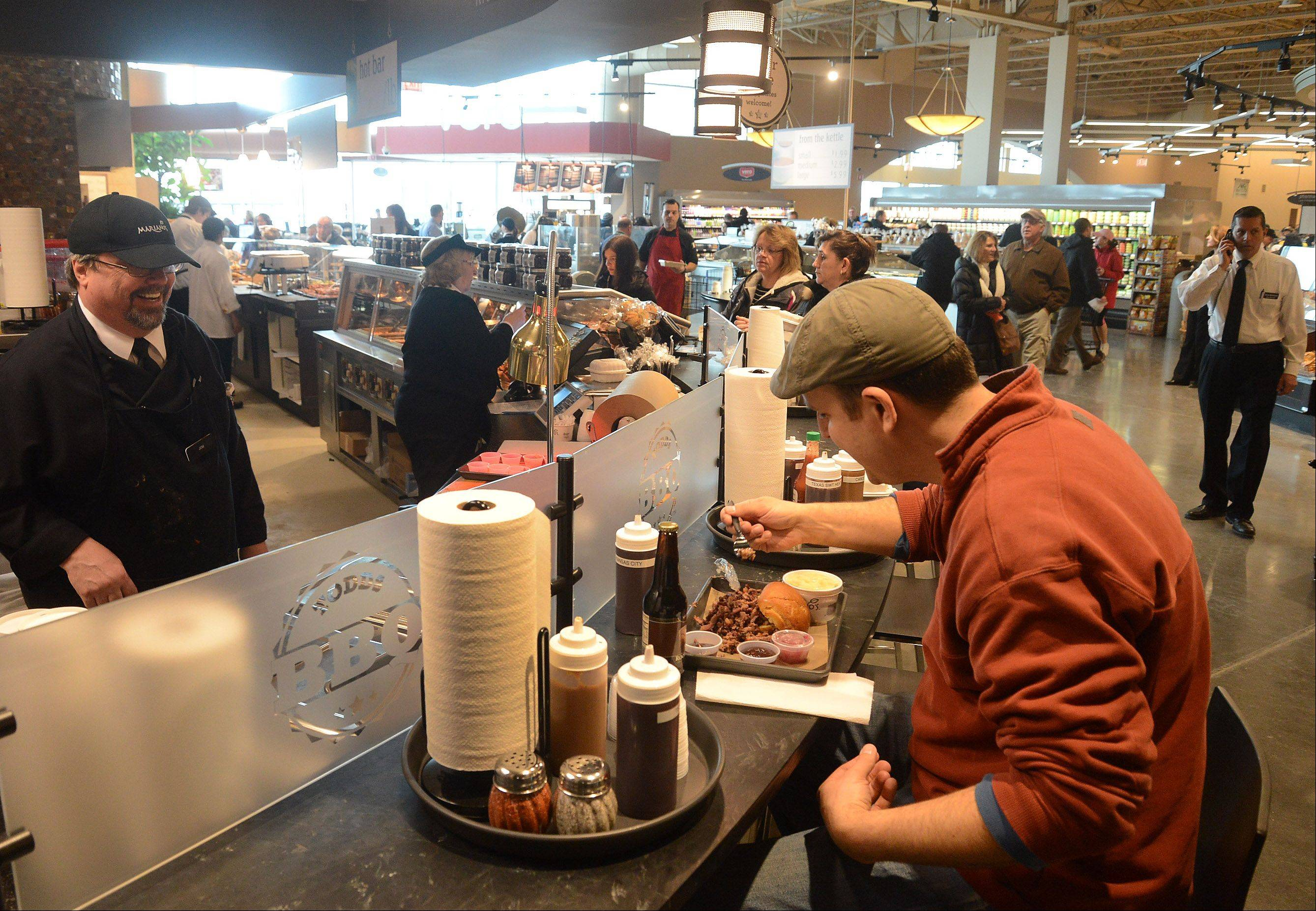Dave Whiteside of Mount Prospect tries out the Smoked Beef Brisket sandwich at Todds BBQ inside the new Lake Zurich Mariano's grocery store that opened Tuesday.
