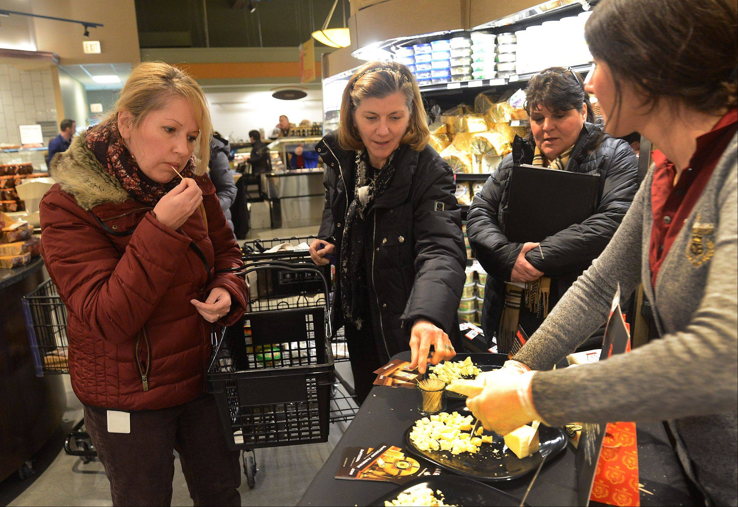 Joanna Renguso, left, of Wauconda, and Susan Kogan, center, of Long Grove, try some Sartori Cheese samples at the new Lake Zurich Mariano's grocery store that opened Tuesday.