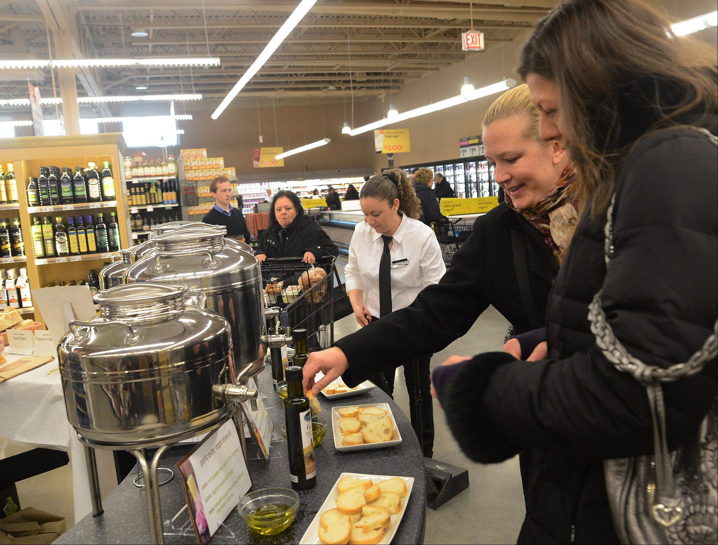 Julie Testin, left, and Christina George, both from Hawthorn Woods, try a sample from the olive oil and vinegar shop at the new Lake Zurich Mariano's grocery store that opened Tuesday.