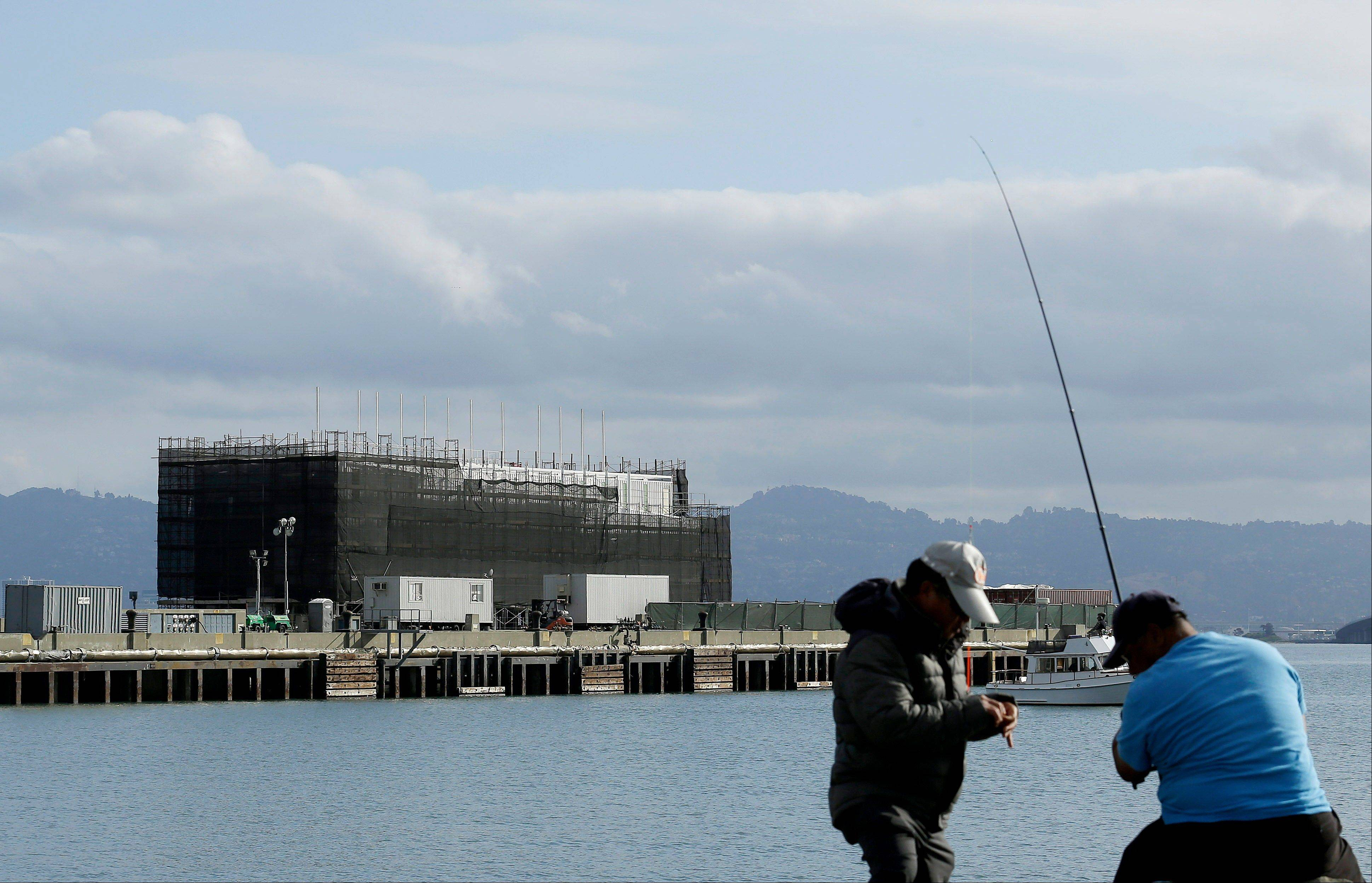 Two men fish in the water in front of a Google barge on Treasure Island in San Francisco. A state agency says Google must move its mystery barge from a construction site on an island in the middle of the San Francisco Bay because the permits are not in order.