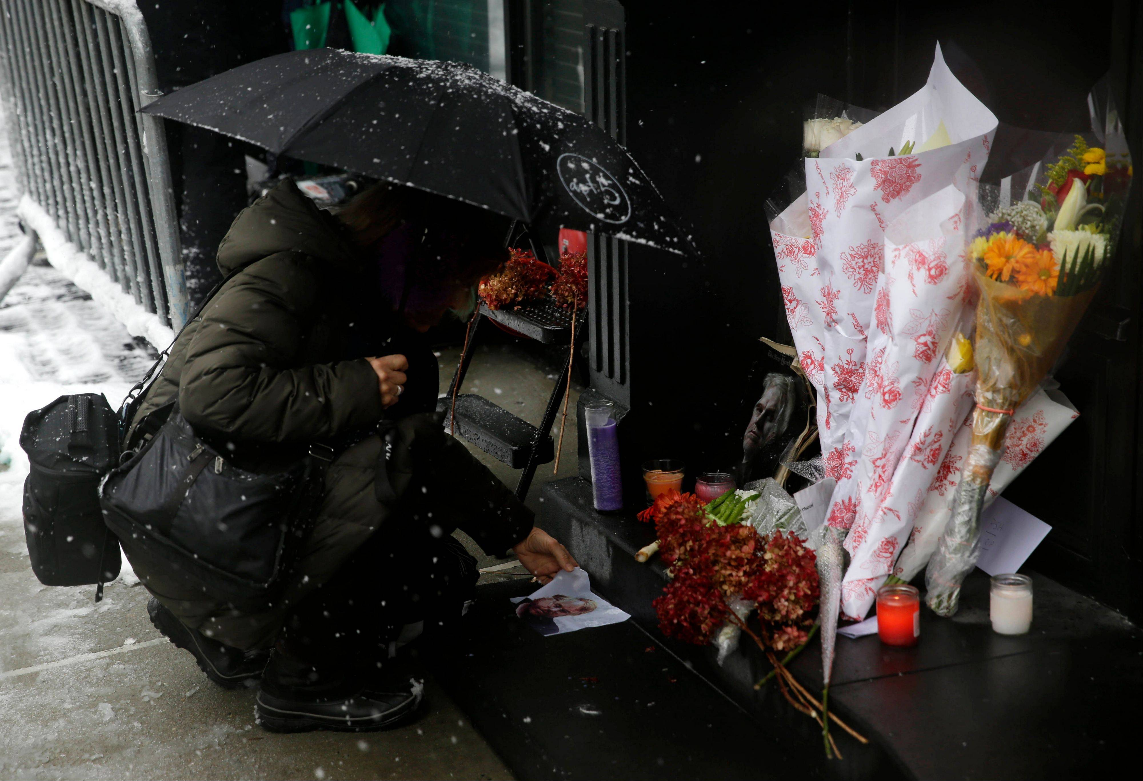 A woman unfolds a picture of Philip Seymour Hoffman at a makeshift memorial in front of the building where his body was found, Monday, Feb. 3, 2014, in New York. Hoffman, 46, was found dead Sunday in his apartment of a suspected drug overdose.