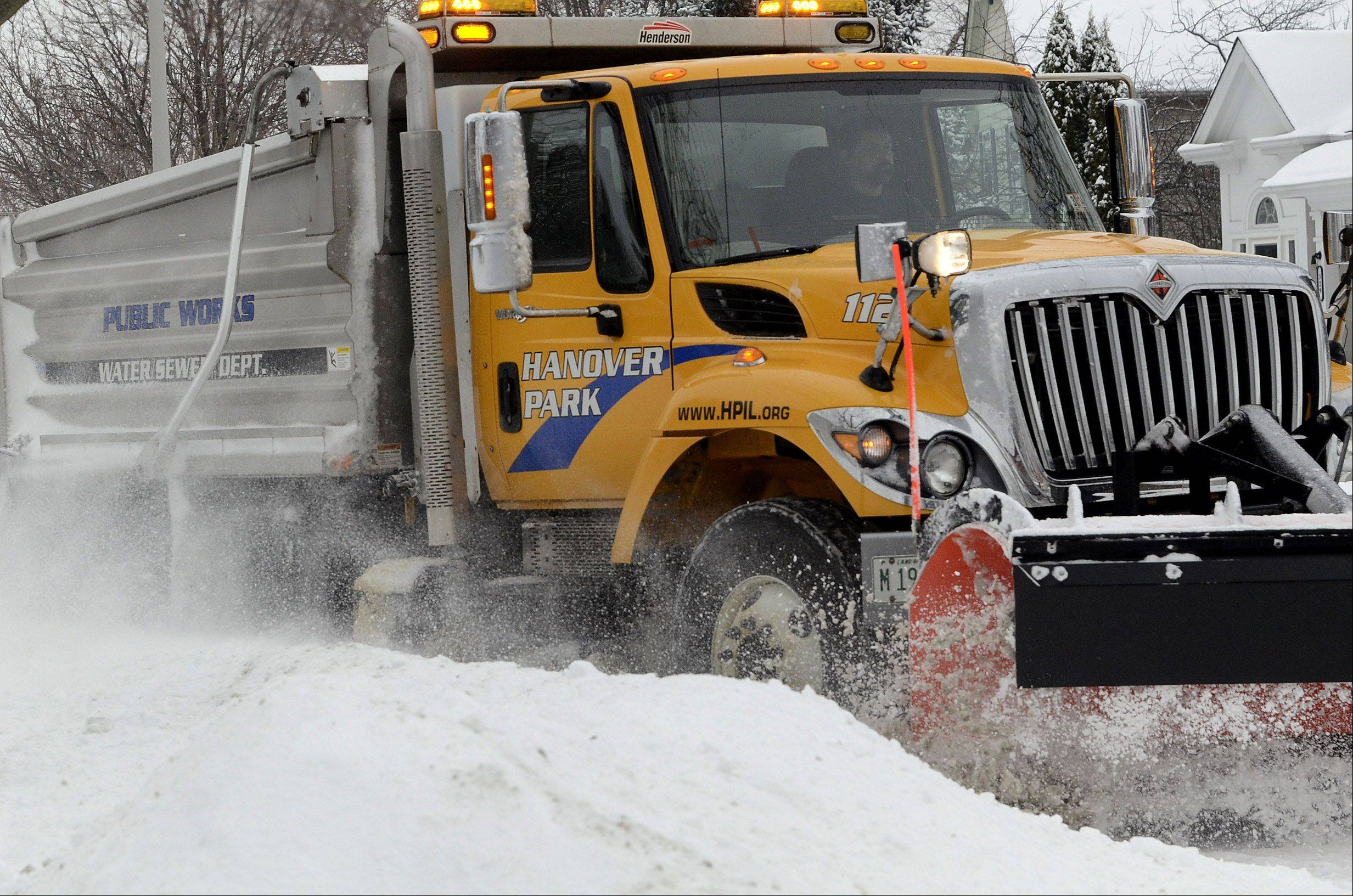 A snow plow clears the street in Hanover Park Saturday morning. State police are warning of slippery roads tonight and overnight.