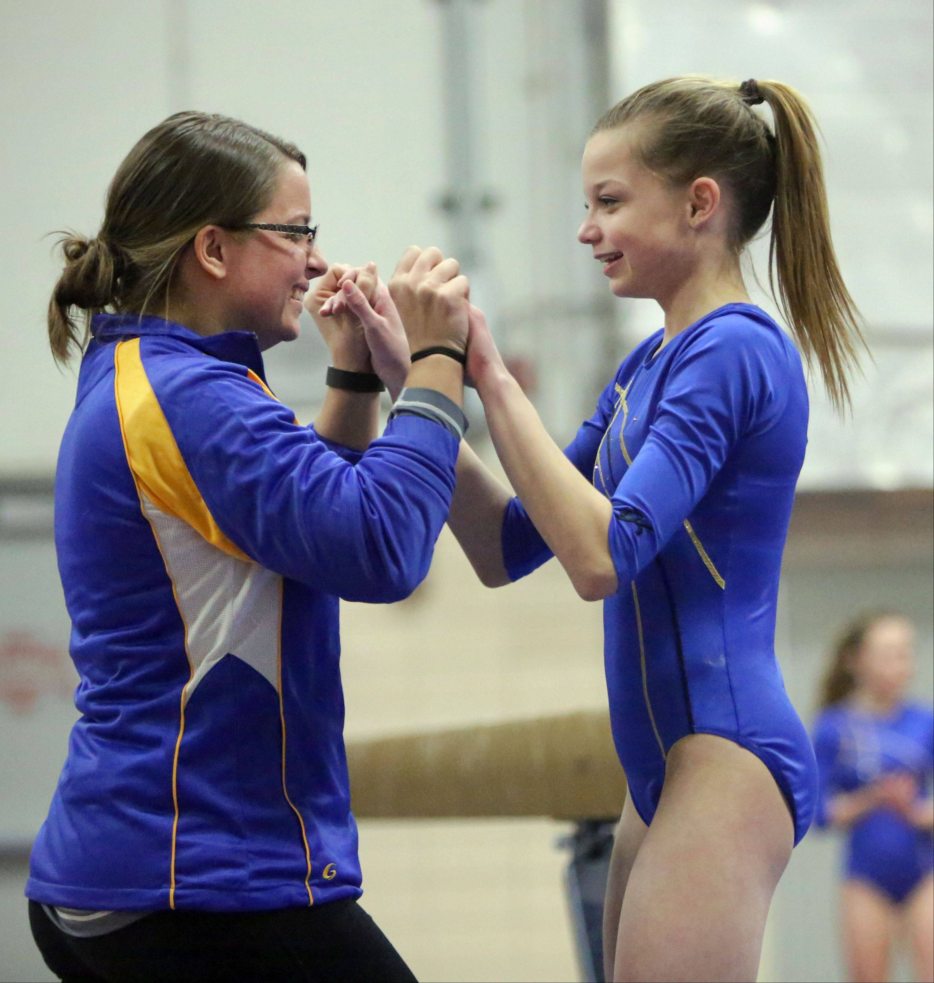 Warren's Hannah Beyrer, right, celebrates with her coach Alison Nardini after her beam routine during Tuesday's regional meet at Deerfield.