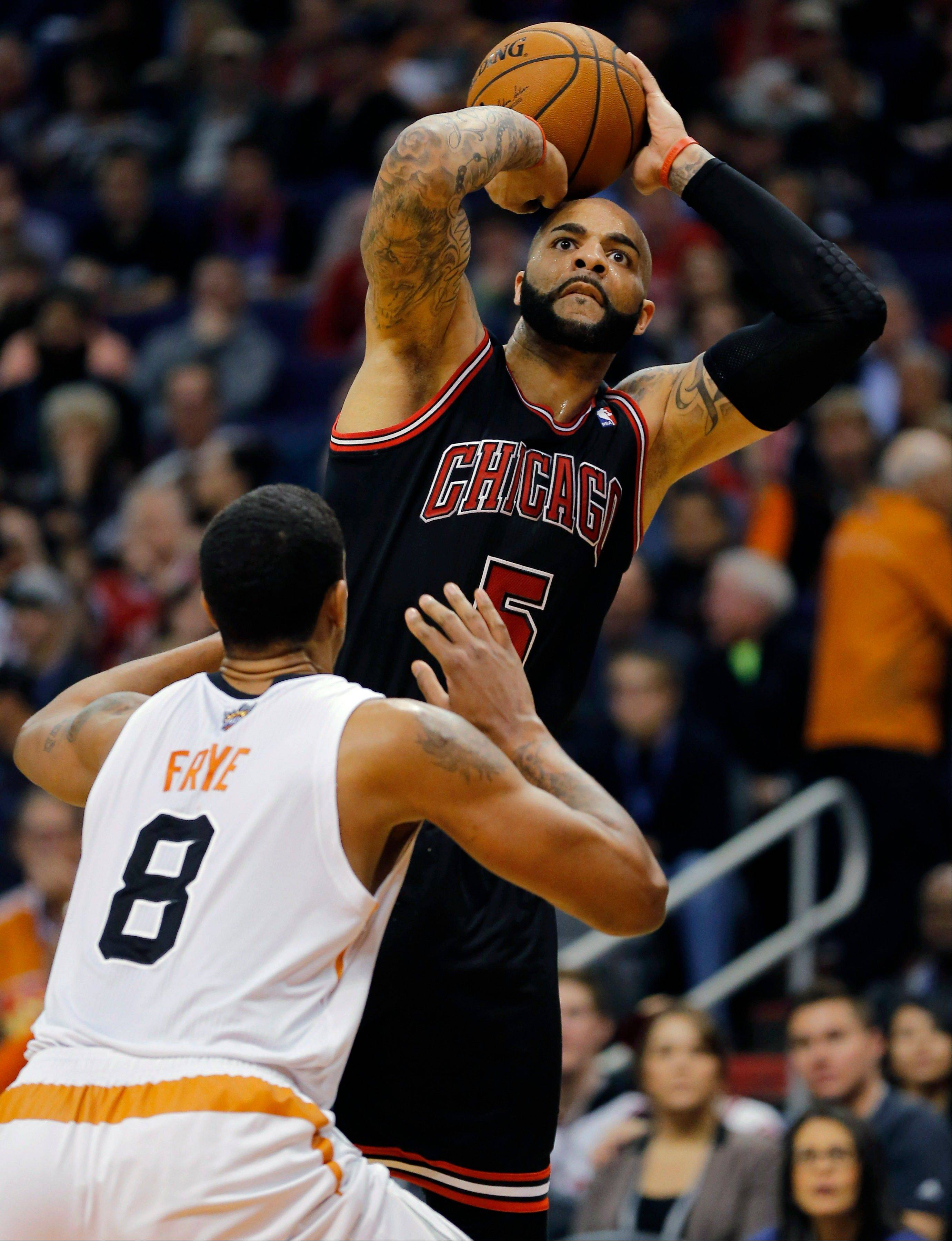 Chicago Bulls' Carlos Boozer (5) shoots over Phoenix Suns' Channing Frye (8) during Tuesday night's game in Phoenix. The Bulls beat the Suns 101-92.