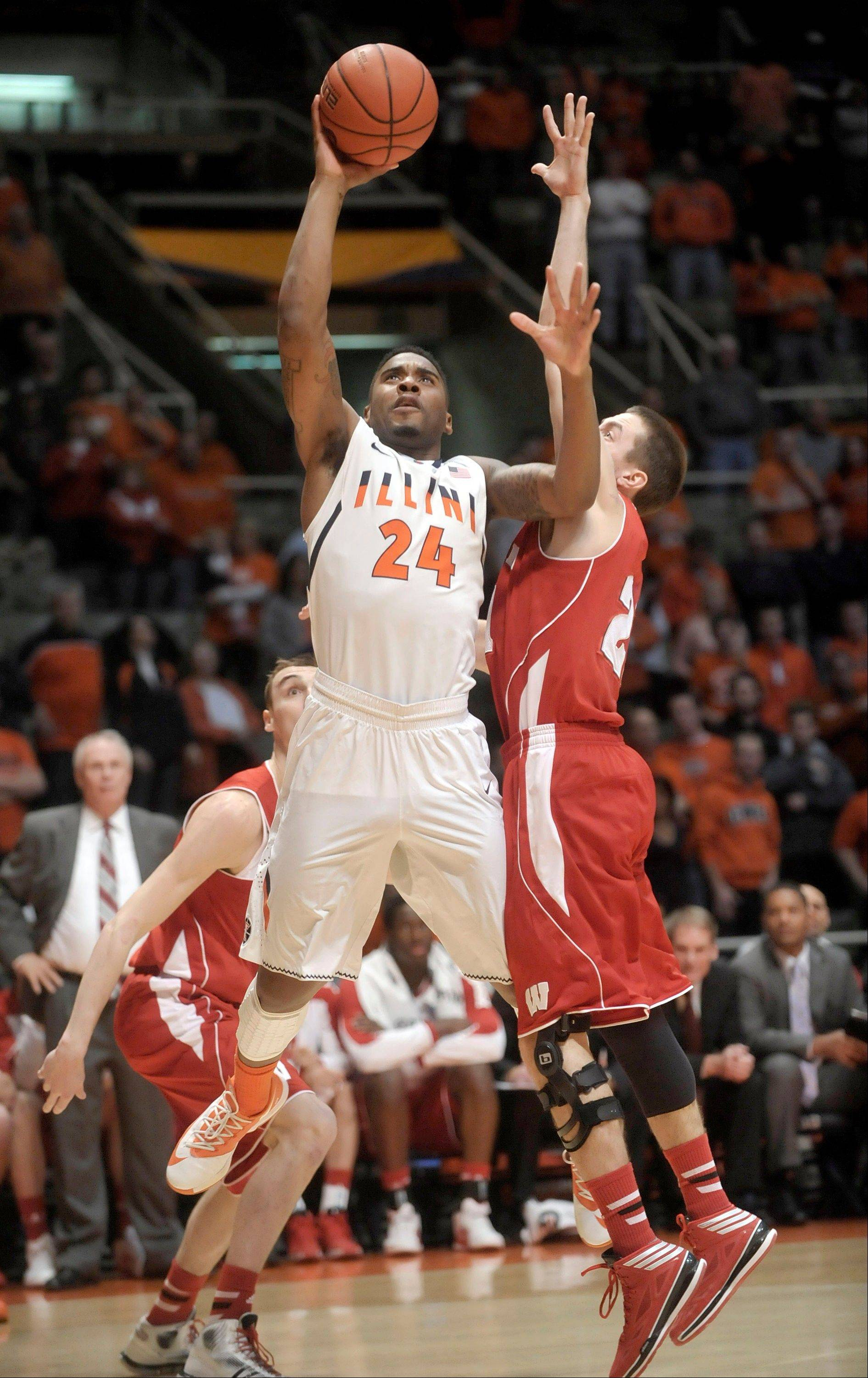 Illinois guard Rayvonte Rice (24) shoots over Wisconsin guard Josh Gasser (21) during Tuesday night's game in Champaign. The Badgers beat the Illini 75-63.