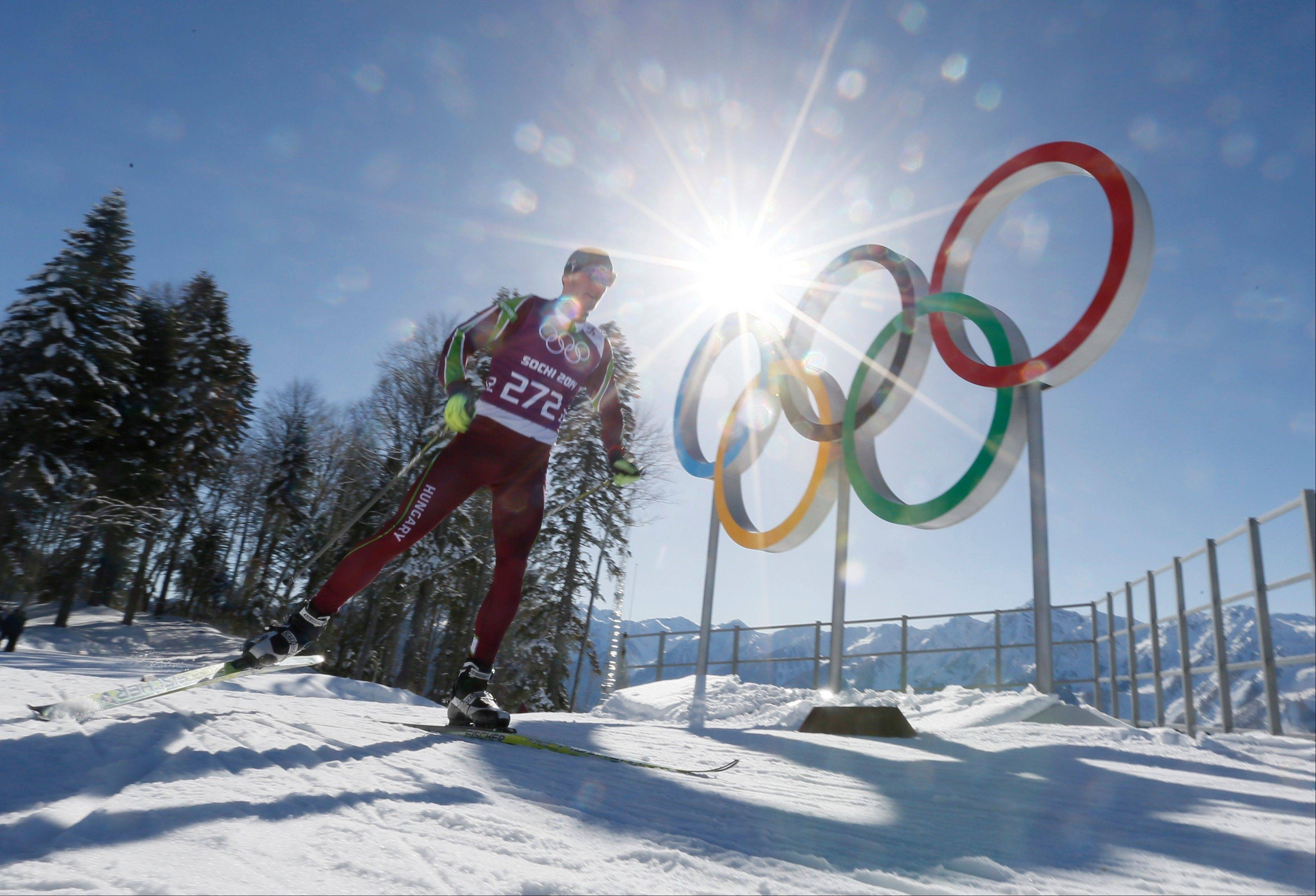 Hungary's Milan Szabo passes by Olympic rings as he trains in the Cross Country stadium of the 2014 Winter Olympics, Tuesday, Feb. 4, 2014, in Krasnaya Polyana, Russia.