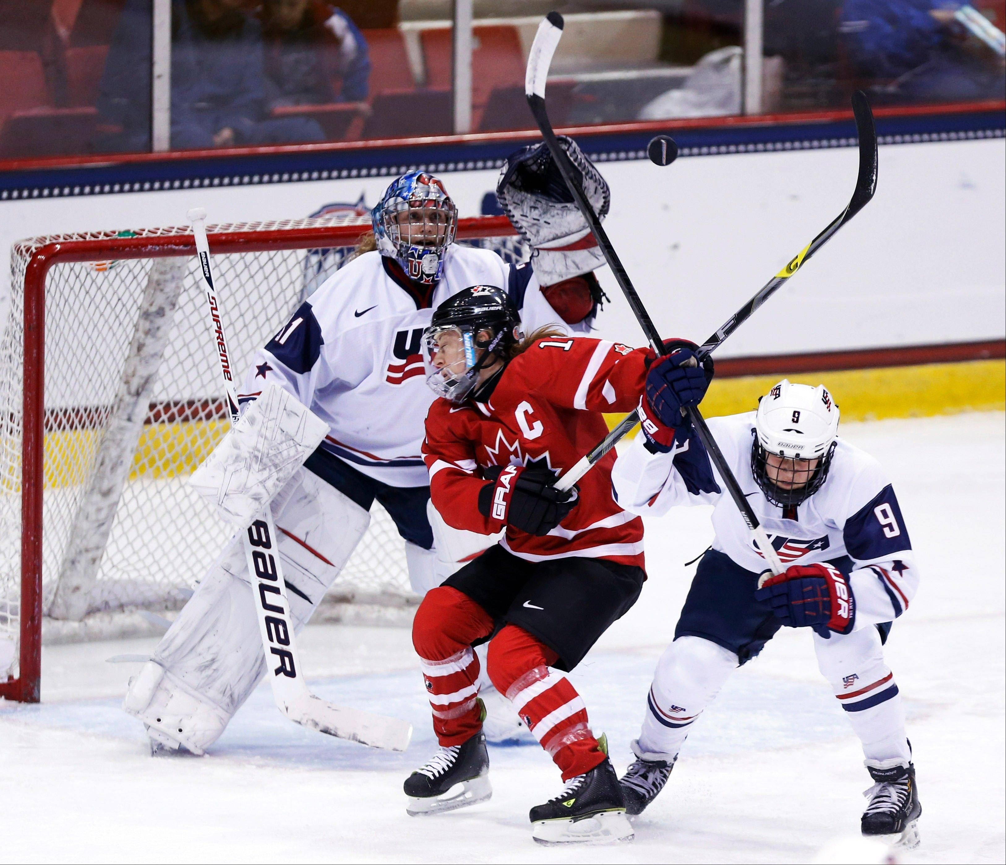 United States goalie Jessie Vetter, left, makes a save in front of teammate Megan Bozek (9) and Canada's Jayna Hefford in a Four Nations Cup women's hockey game last November. The U.S. team, with Buffalo Grove native Bozek, opens its Olympic play on Saturday.