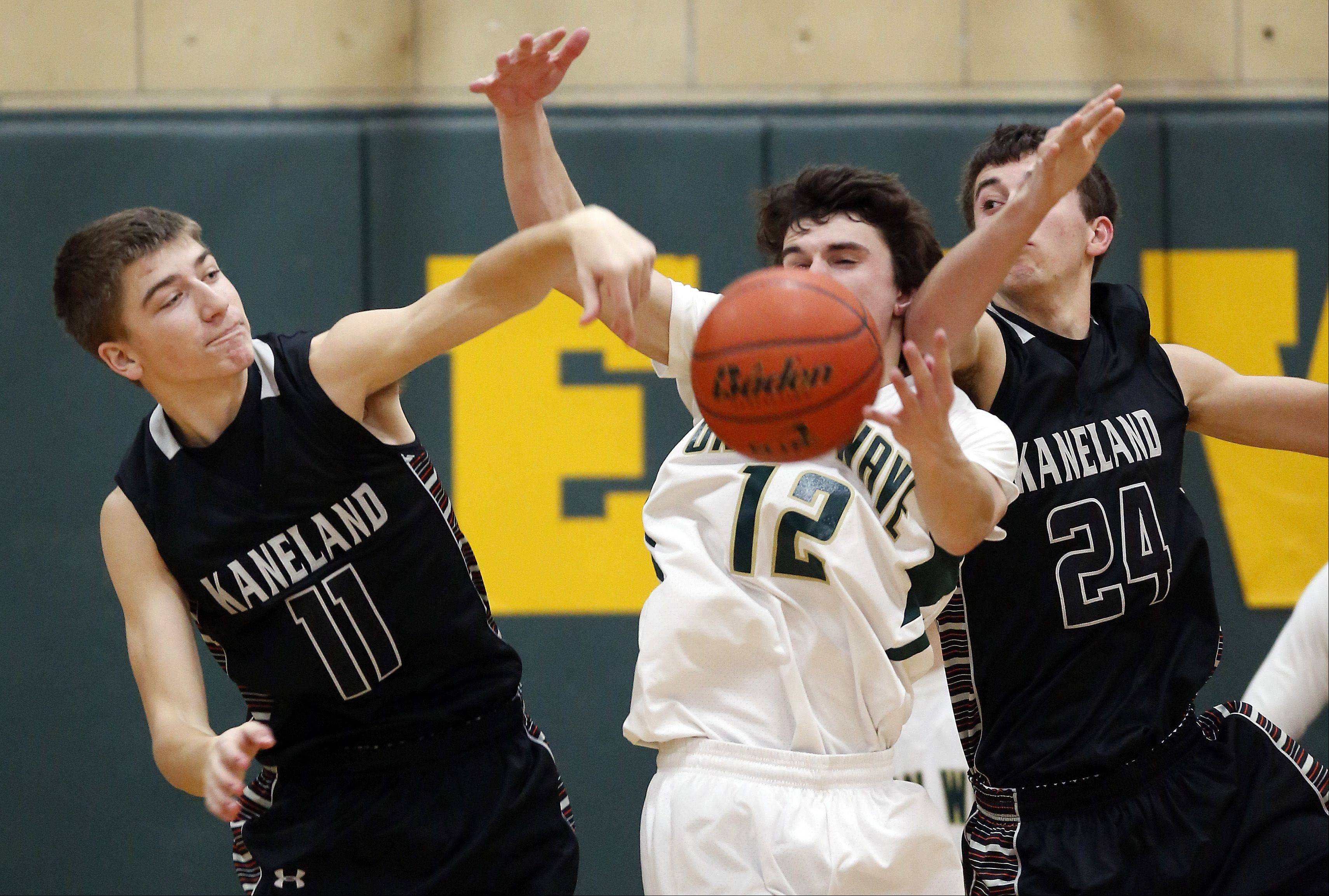 Kaneland's Steven Limbrunner (11) and Ryan David (24) battle St. Edward's Joseph French (12) Friday in Elgin.