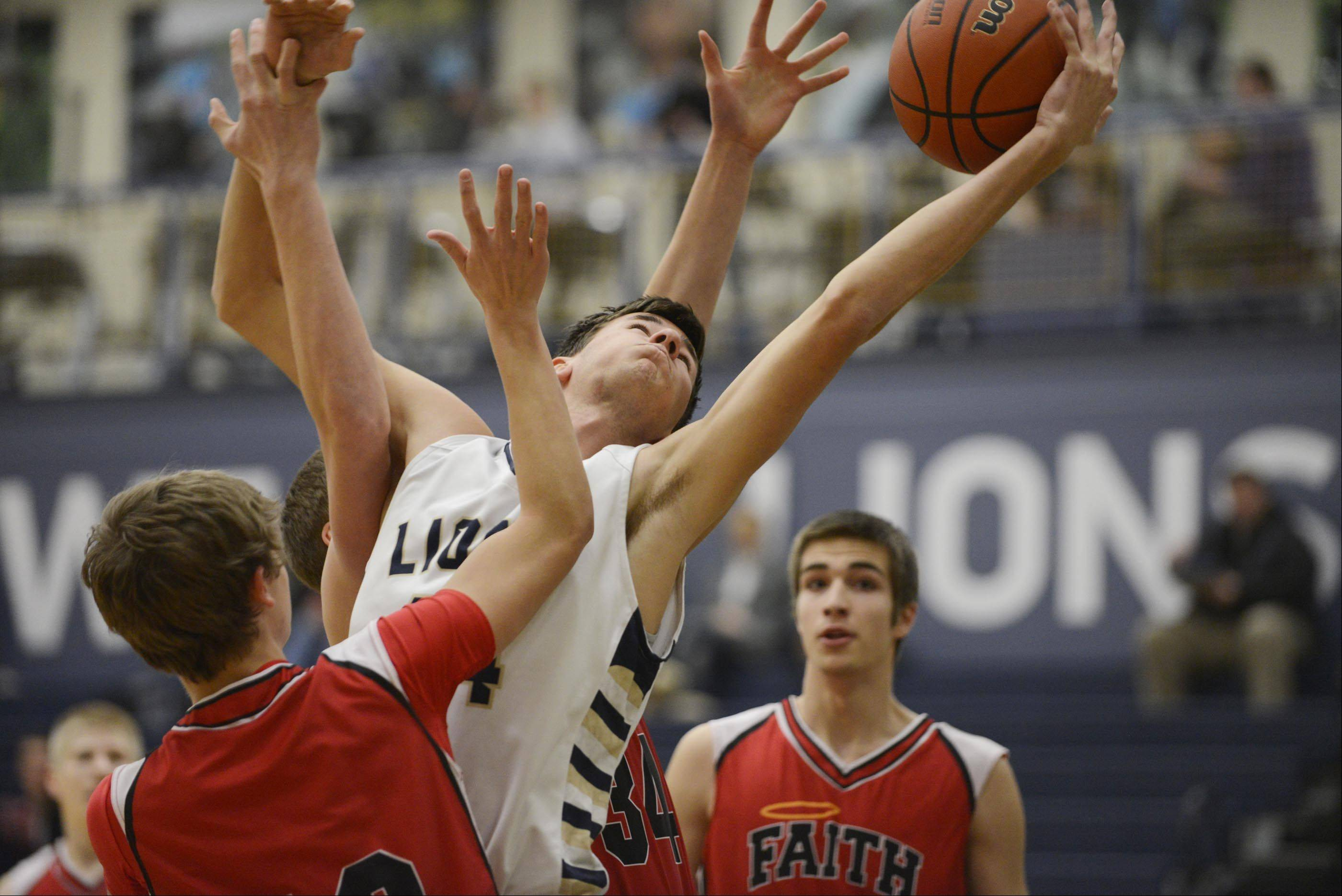 Harvest Christian Academy's John Vislisel stretches for a rebound against Faith Lutheran Thursday in Elgin.
