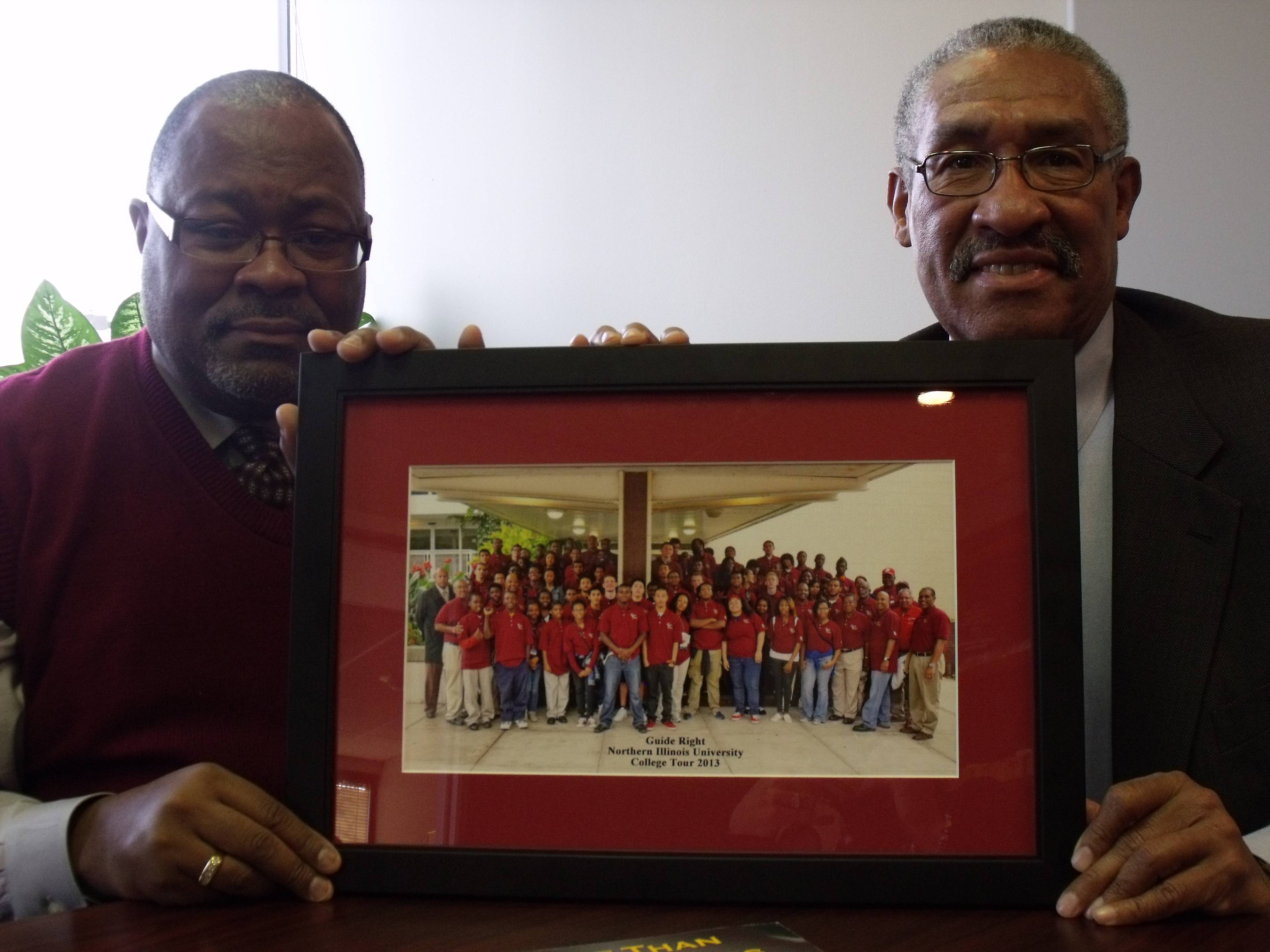 Diamond Youth Foundation Board Members James Jackson (left) and Robert Engram proudly display a photo of the 80 students who attended a recent college visit to Northern Illinois University.  The students participate in the Diamond Youth Foundation at their respective high schools.