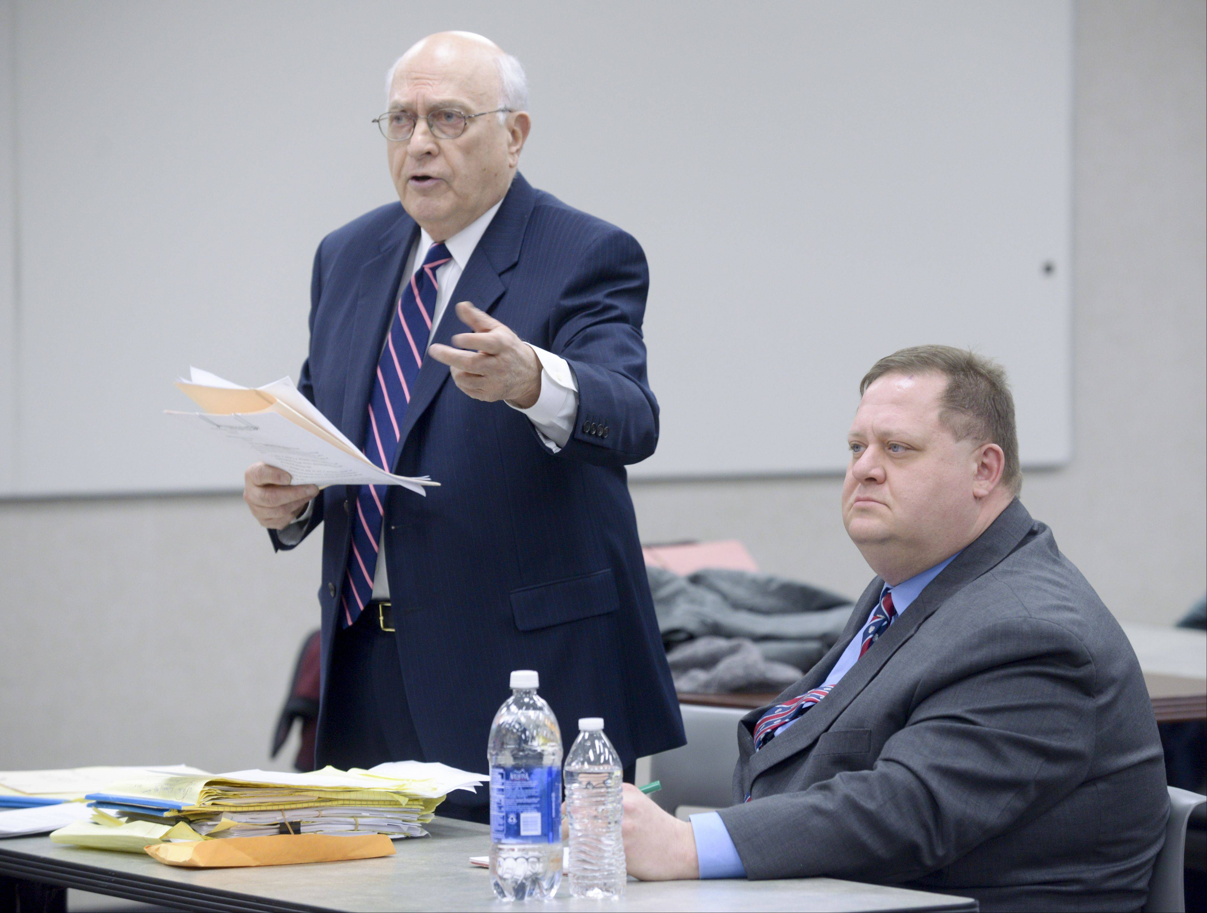 Attorney Aldo Botti speaks during the opening day of the termination hearing for his client, Carol Stream Fire Protection District Battalion Chief Joe Gilles, seated at right.