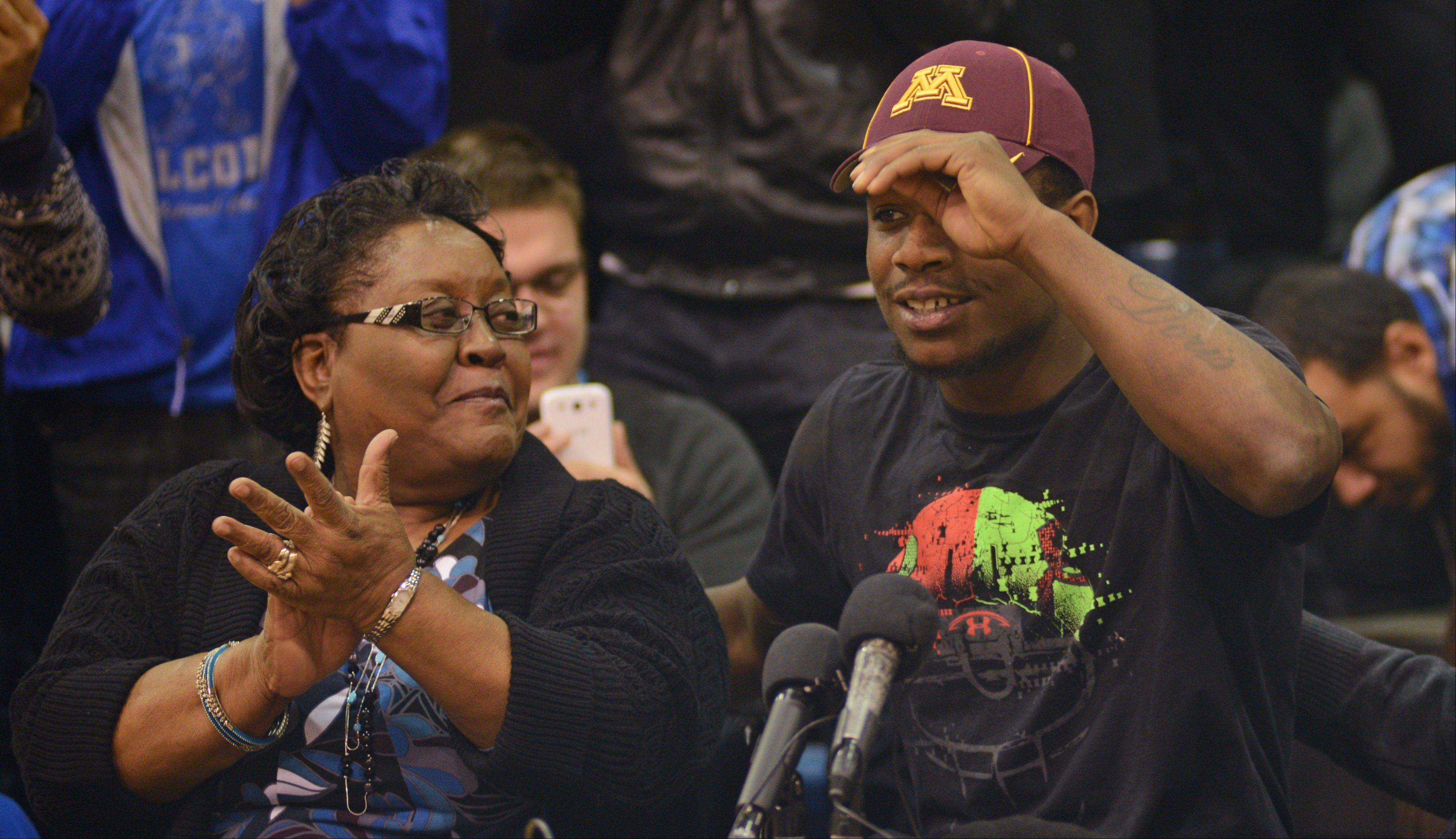 Jeff Jones, a running back from Minneapolis Washburn, puts on a Minnesota cap while his grandmother Doris Jones applauds, Wednesday, Feb. 5, 2014, in Minneapolis. Jones upheld his verbal commitment to the program by announcing his decision Wednesday on national signing day to join the Gophers football team. (AP Photo/Star Tribune, Richard Sennott) ST. PAUL OUT MINNEAPOLIS-AREA TV OUT MAGS OUT