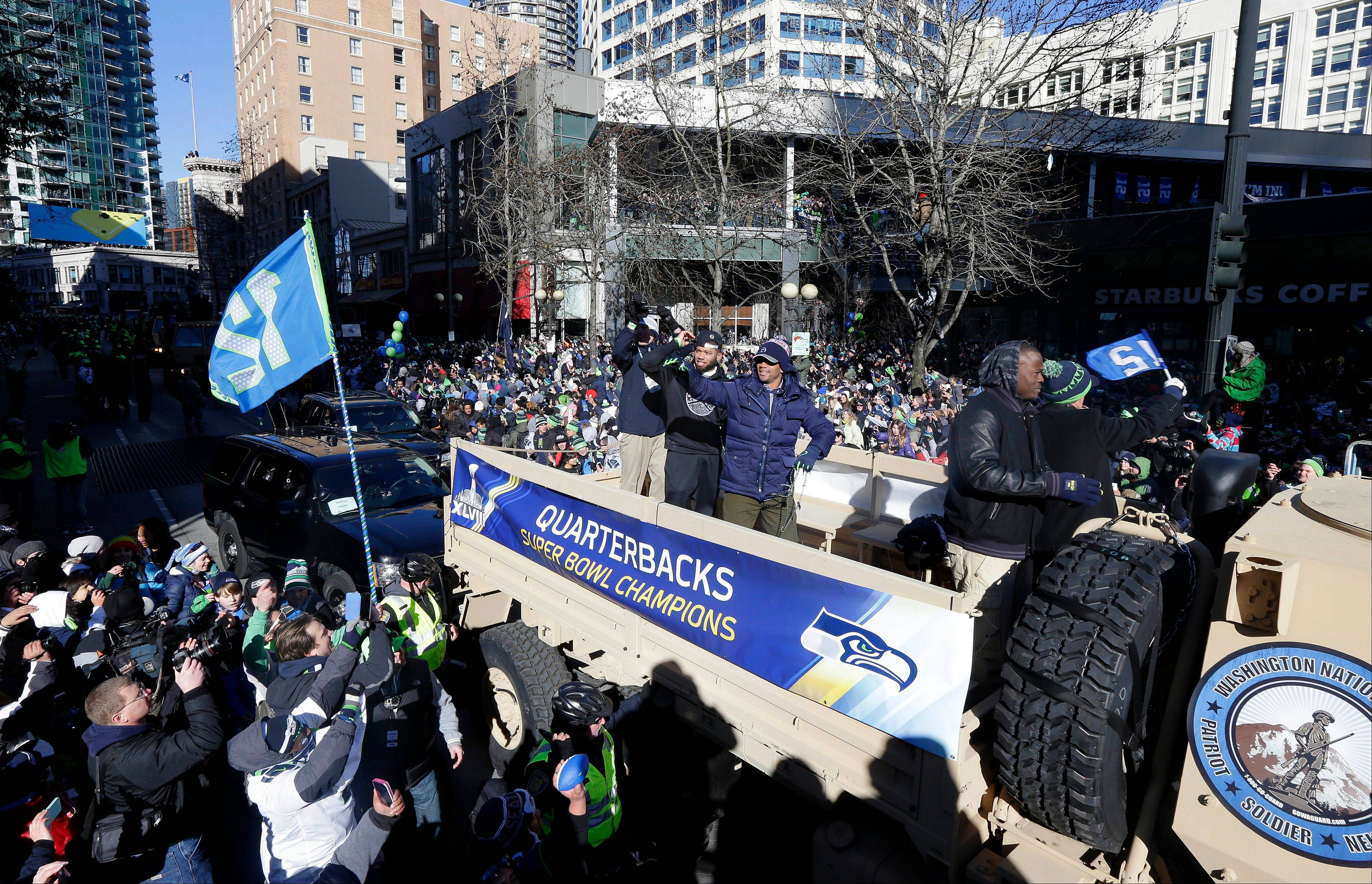 Seattle Seahawks quarterback Russell Wilson, center, waves to fans during the Super Bowl champions parade on Wednesday, Feb. 5, 2014, in Seattle. The Seahawks defeated the Denver Broncos 43-8 in NFL football's Super Bowl XLVIII on Sunday. (AP Photo/Ted S. Warren)