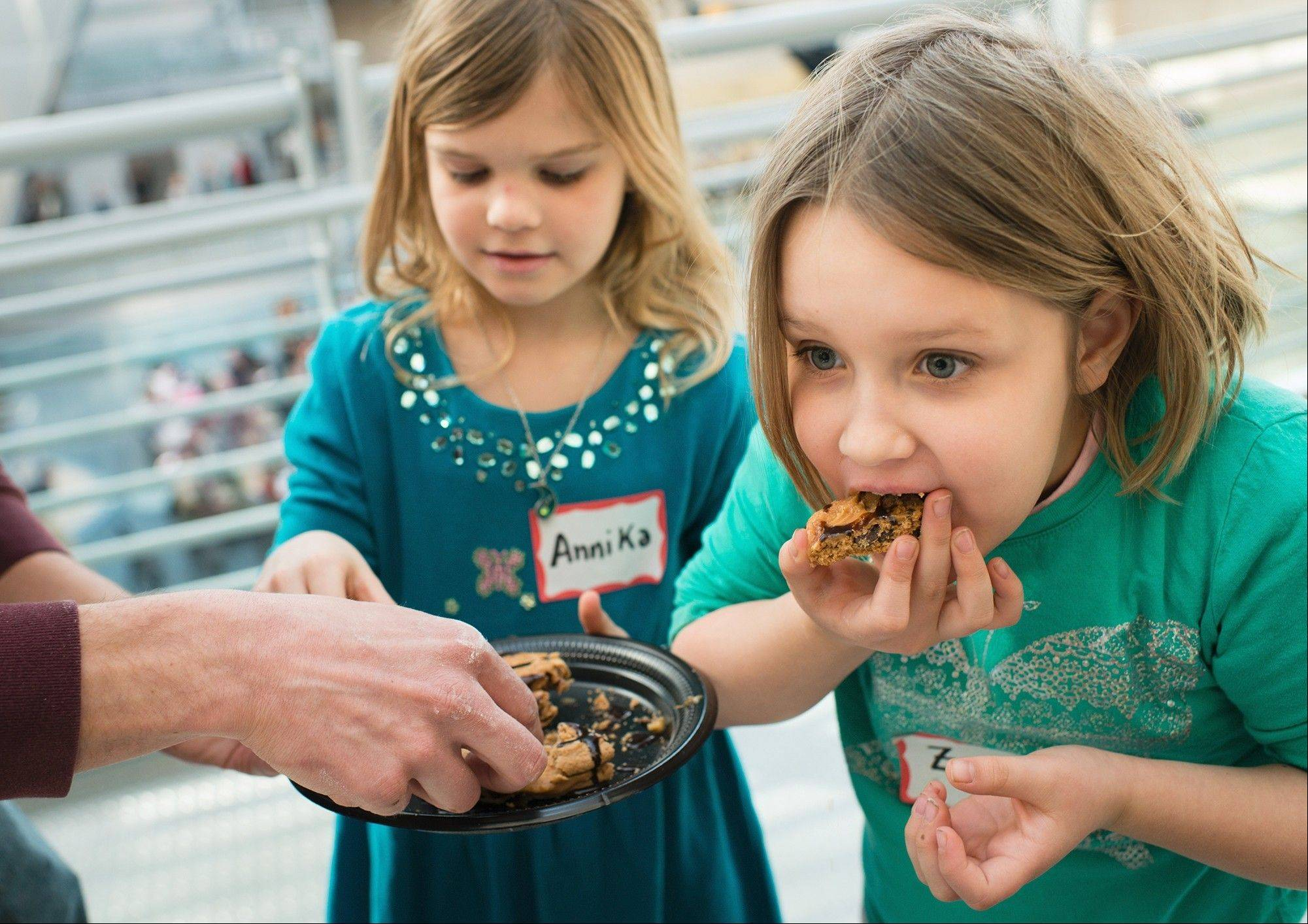 Annika Pugh, 8, and her sister Zoe, 7, of Chantilly, Va., eat a peanut butter-chocolate cookie sandwich they helped their father make for the second annual Meal-Ready-To-Eat/MRE cook-off Saturday. Their father, Marine Capt. Douglas Pugh, who is stationed in North Carolina at Marine Corps Air Station Cherry Point, won the contest's best entree award with a chicken pesto pasta dish.