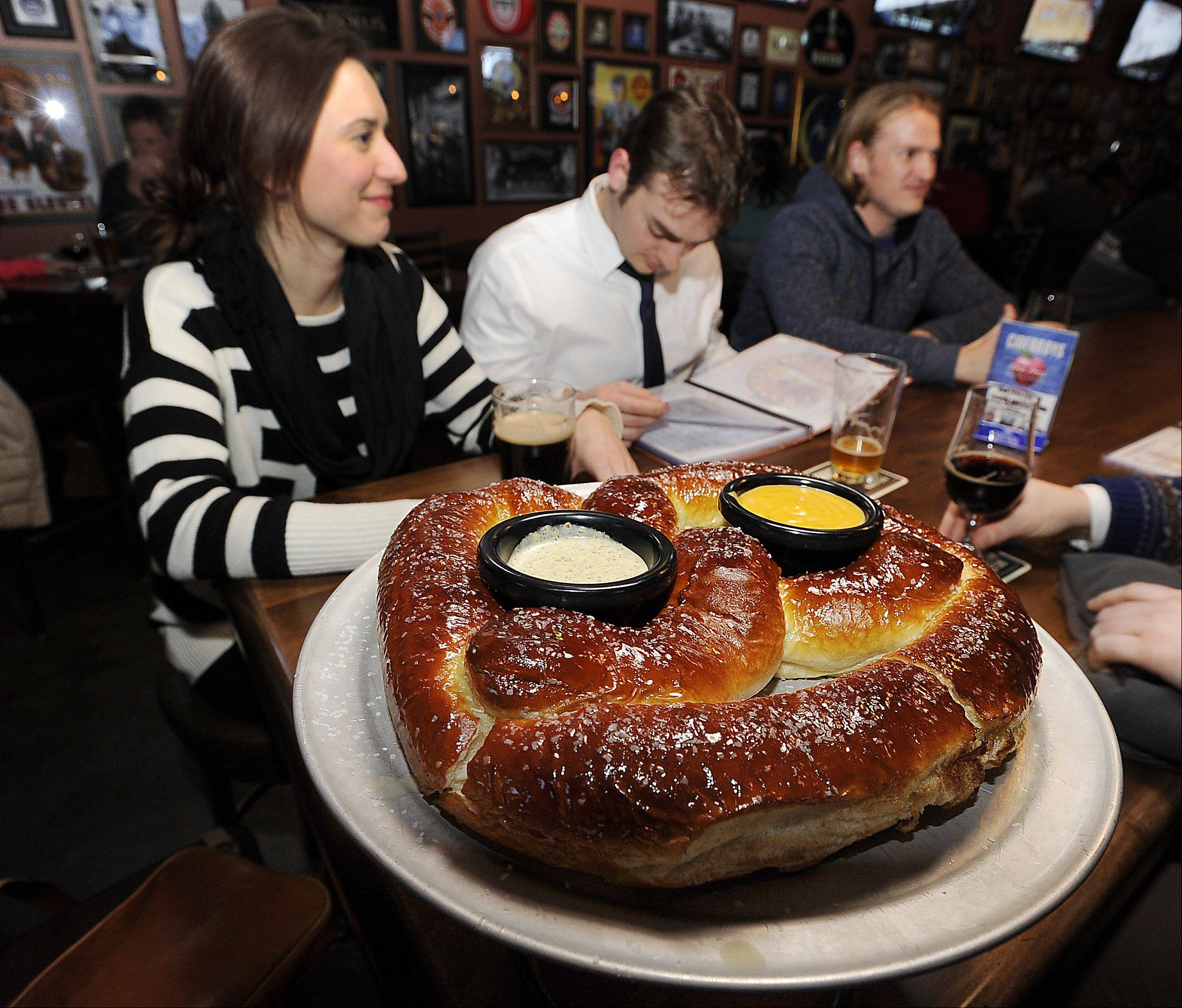 A giant pretzel, served with dipping sauces, is meant to be shared at The Beer Market in Schaumburg.