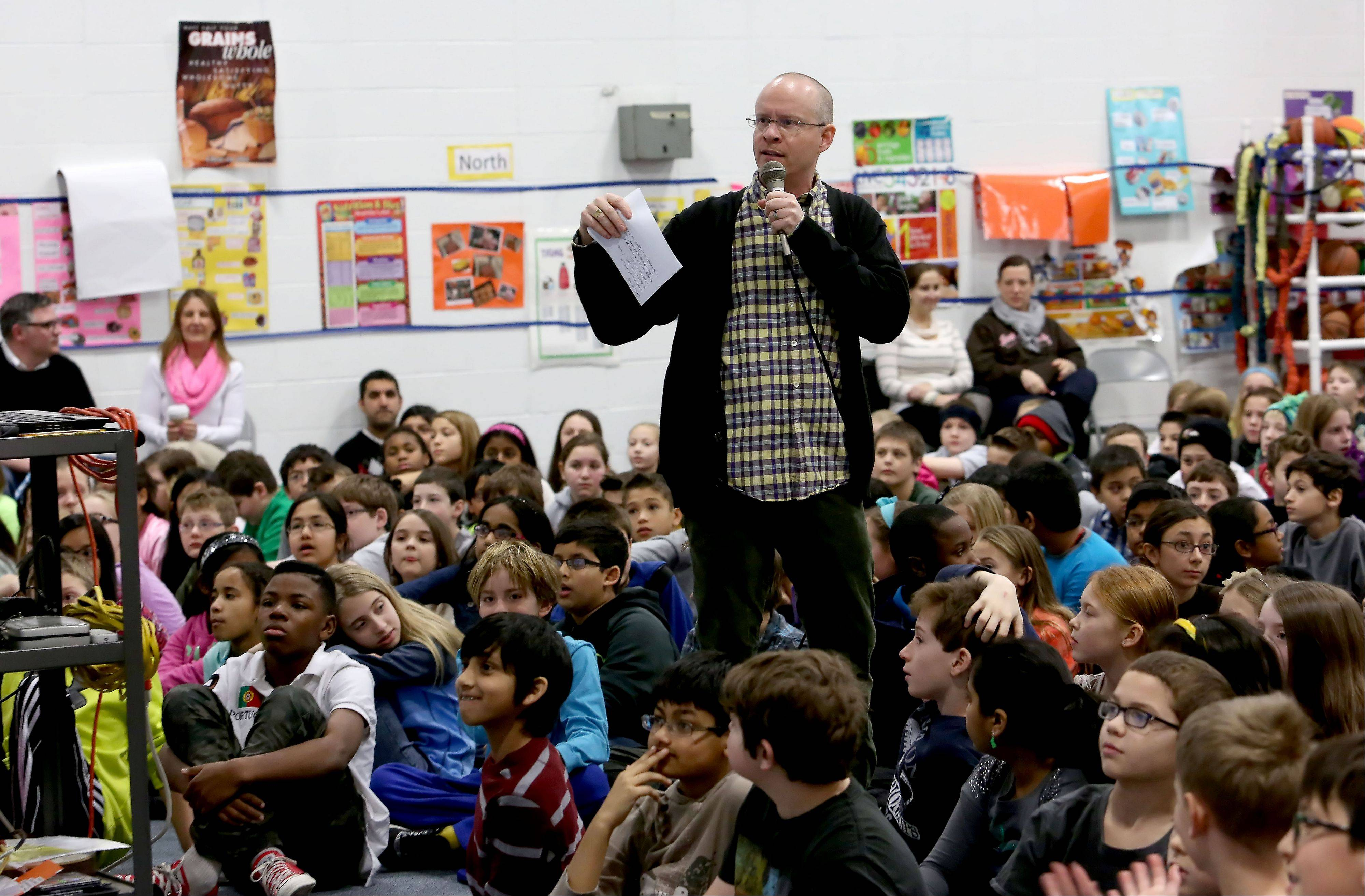 Author Tom Watson asks questions Wednesday of fourth- and fifth-grade students from May Watts and Steck elementary schools in Indian Prairie District 204 who gathered for a pep rally-style celebration of reading as part of Naperville READS. This year's program brought 12 children's authors to Naperville schools in groups of three.