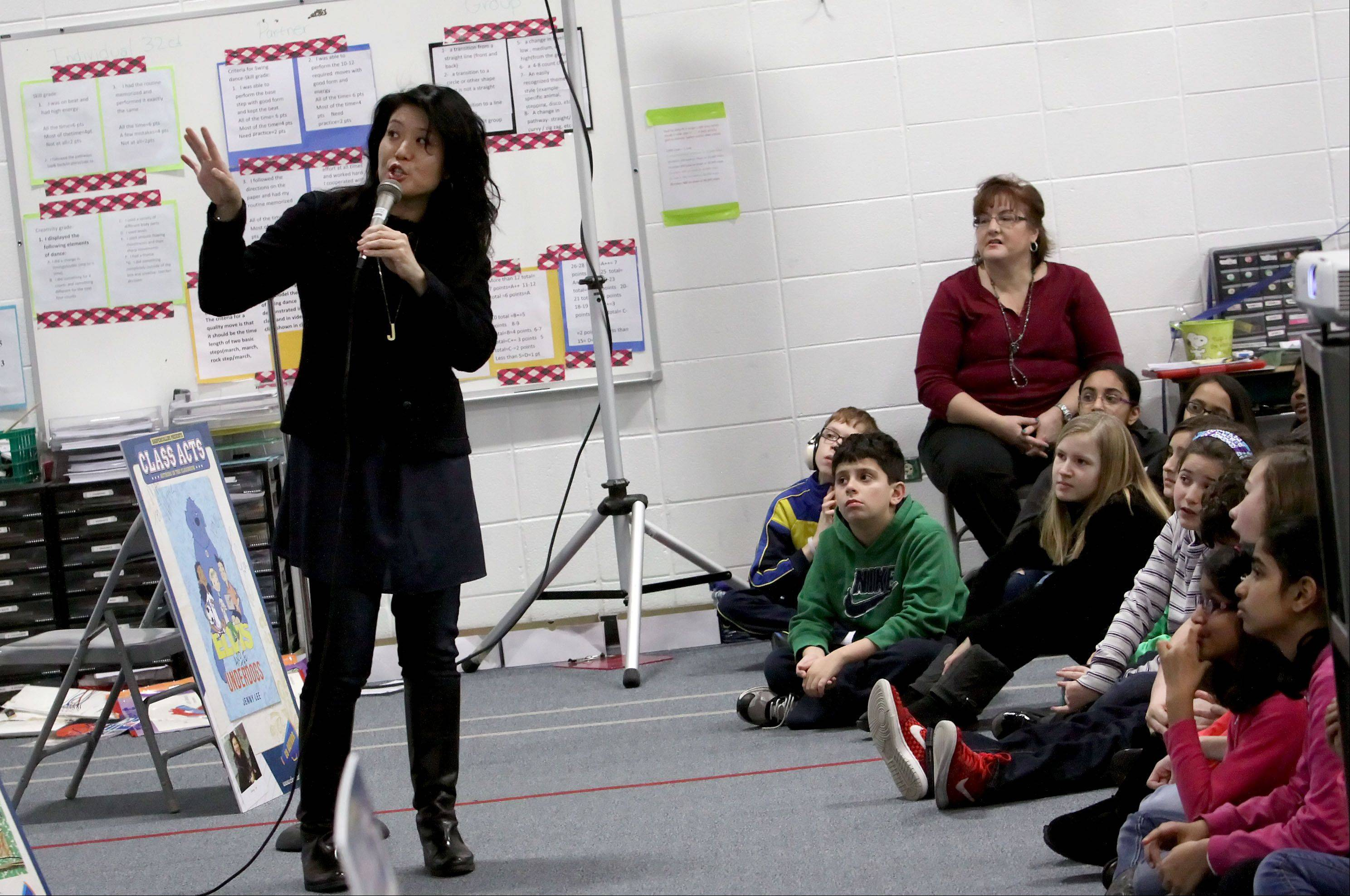 "Author Jenny Lee discusses her book ""Elvis and the Underdogs"" on Wednesday during a Naperville READS assembly for fourth- and fifth-grade students from May Watts and Steck elementary schools in Indian Prairie Unit District 204."