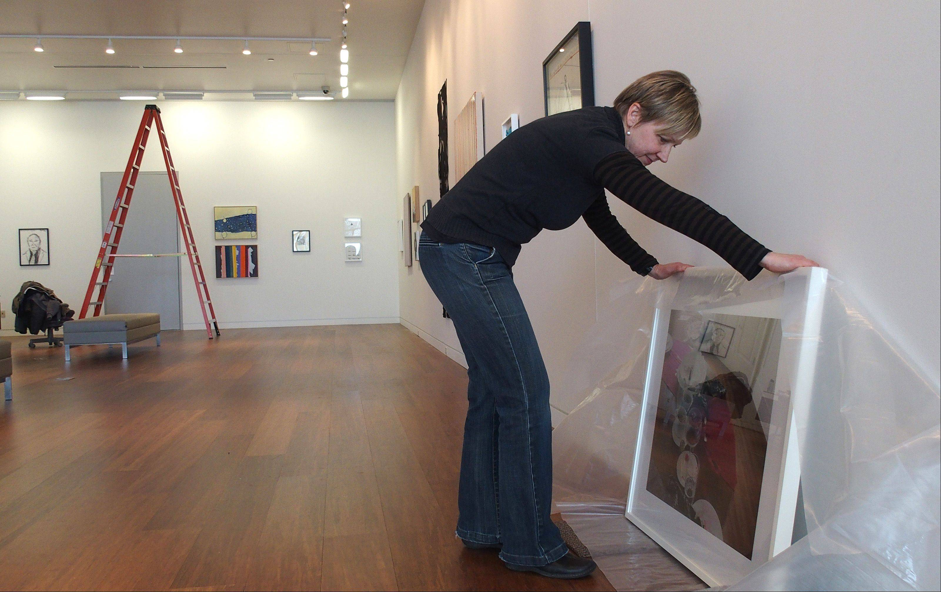 Curator Barb Wiesen prepares a painting for hanging Wednesday at the new Cleve Carney Art Gallery at the College of DuPage. The initial exhibition will feature works from the collection of the gallery's namesake, a businessman and art lover from Wheaton.