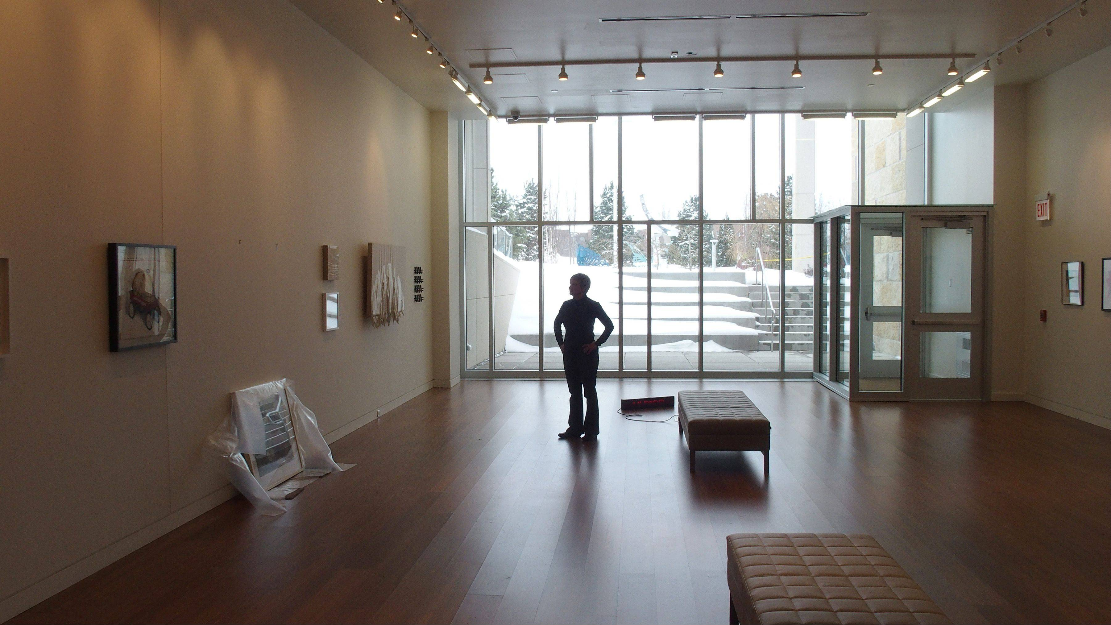 The gallery features high ceilings, heated sustainable bamboo floors and an outdoor courtyard visible through glass windows.
