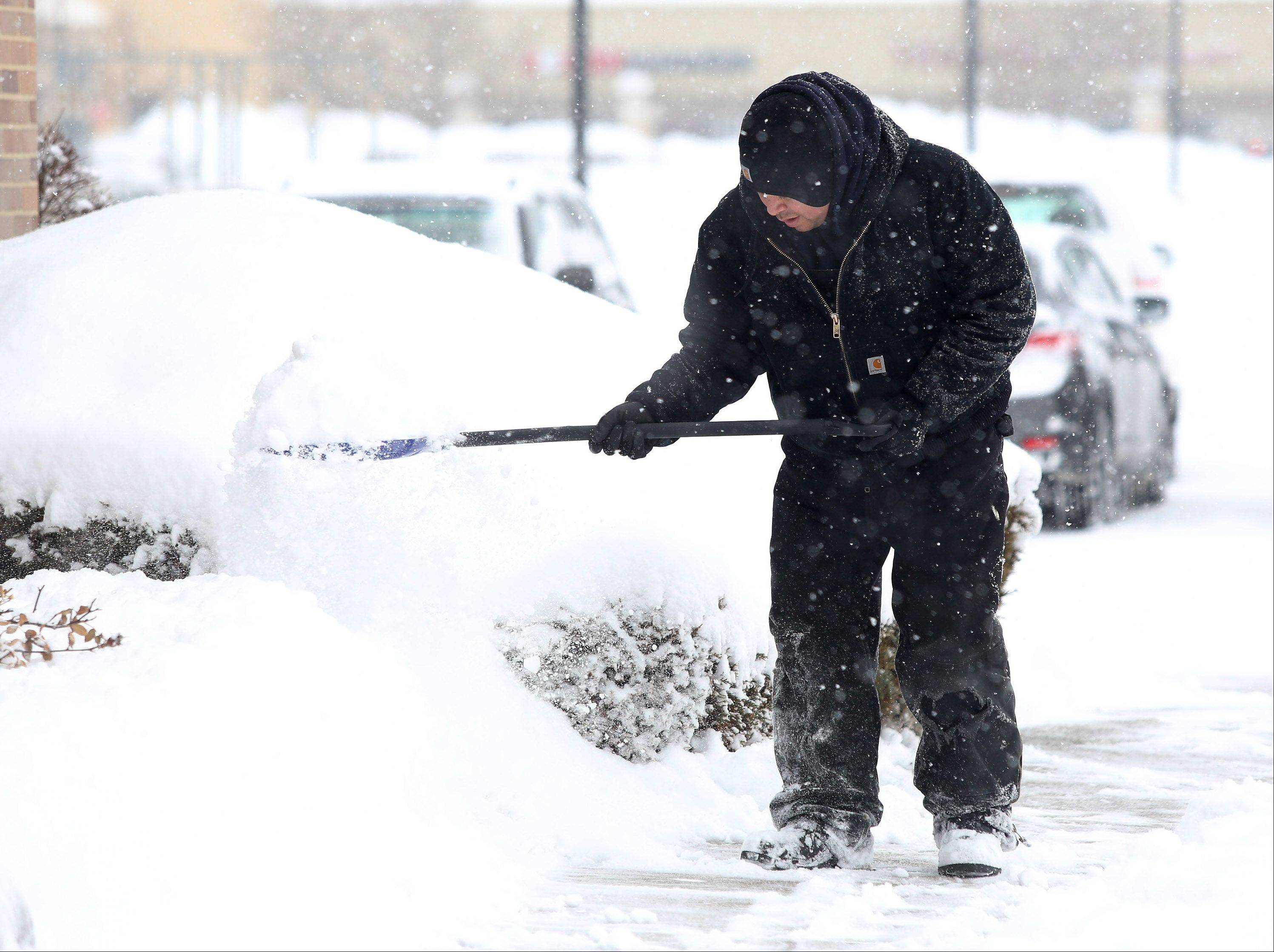 Pedro Castrejon of Martin & Associates Landscaping shovels sidewalks in front of businesses in Woodland Commons in Buffalo Grove on Wednesday. The overnight snowstorm forced area residents to once again dig out their driveways and face morning traffic problems on commutes to work and school.