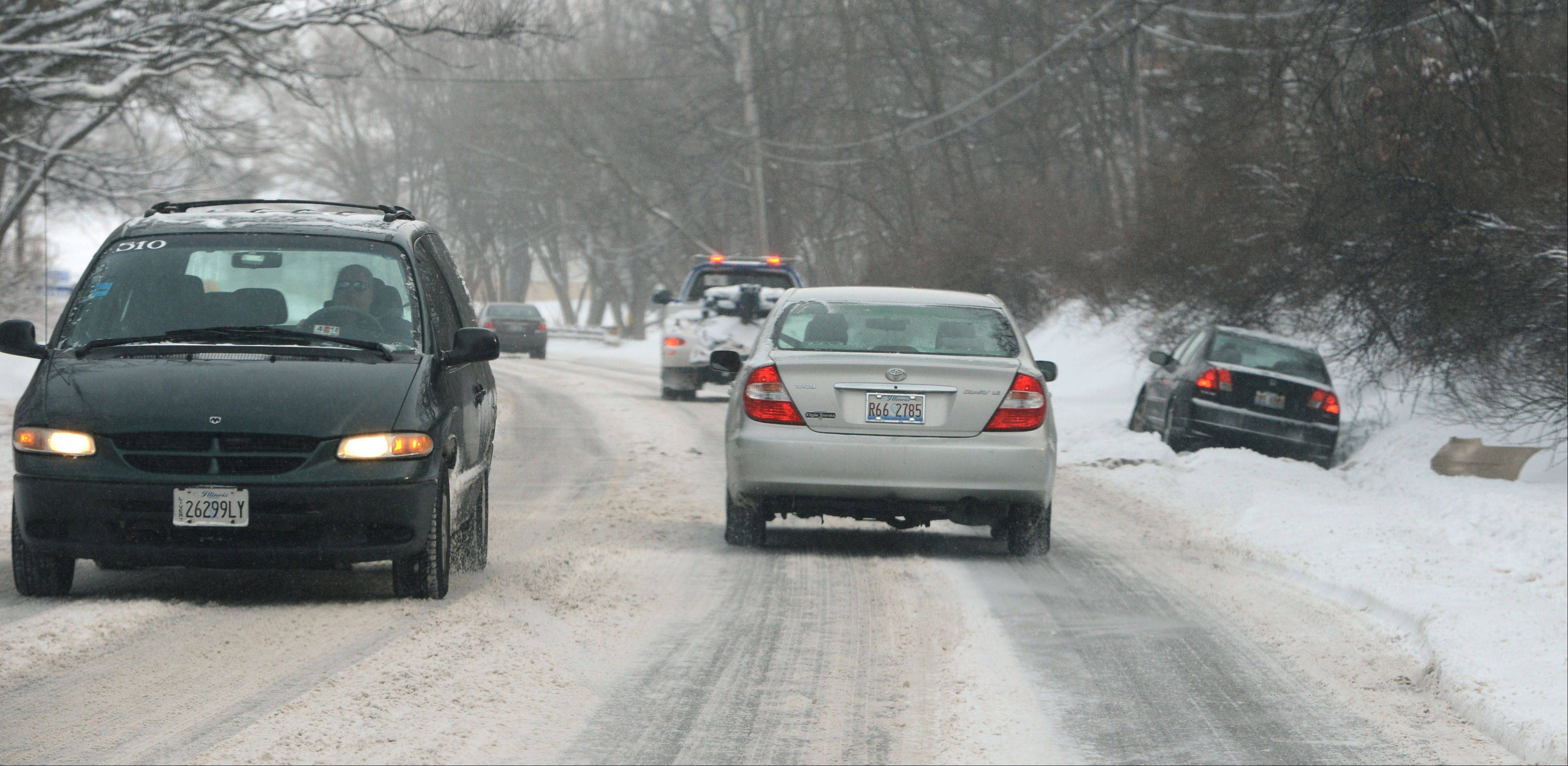 A driver gets stuck in a ditch and waits for a tow truck along Route 176 just west of Island Lake Wednesday morning.