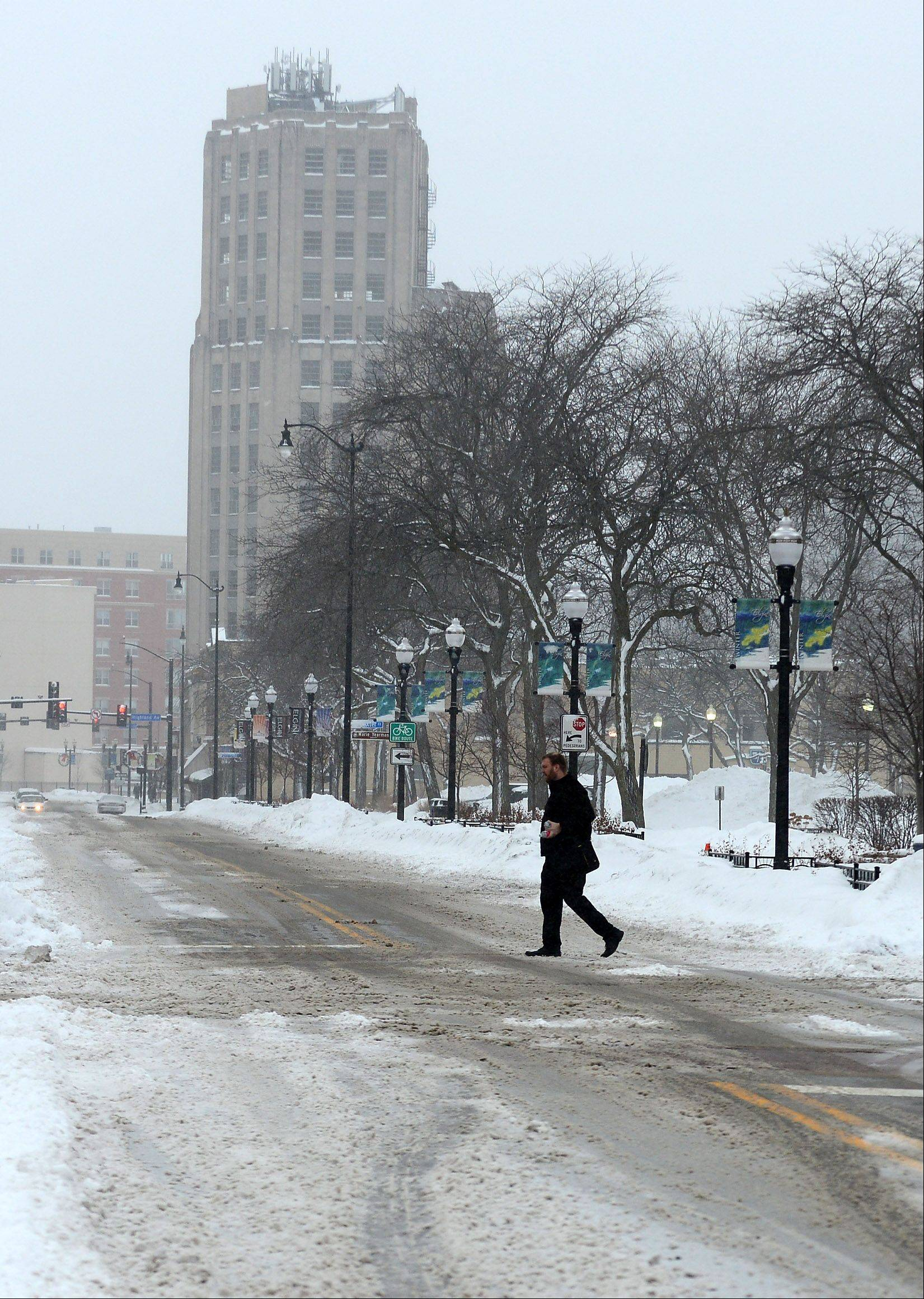 A man crosses a snowy Douglas Avenue in Elgin Wednesday morning.
