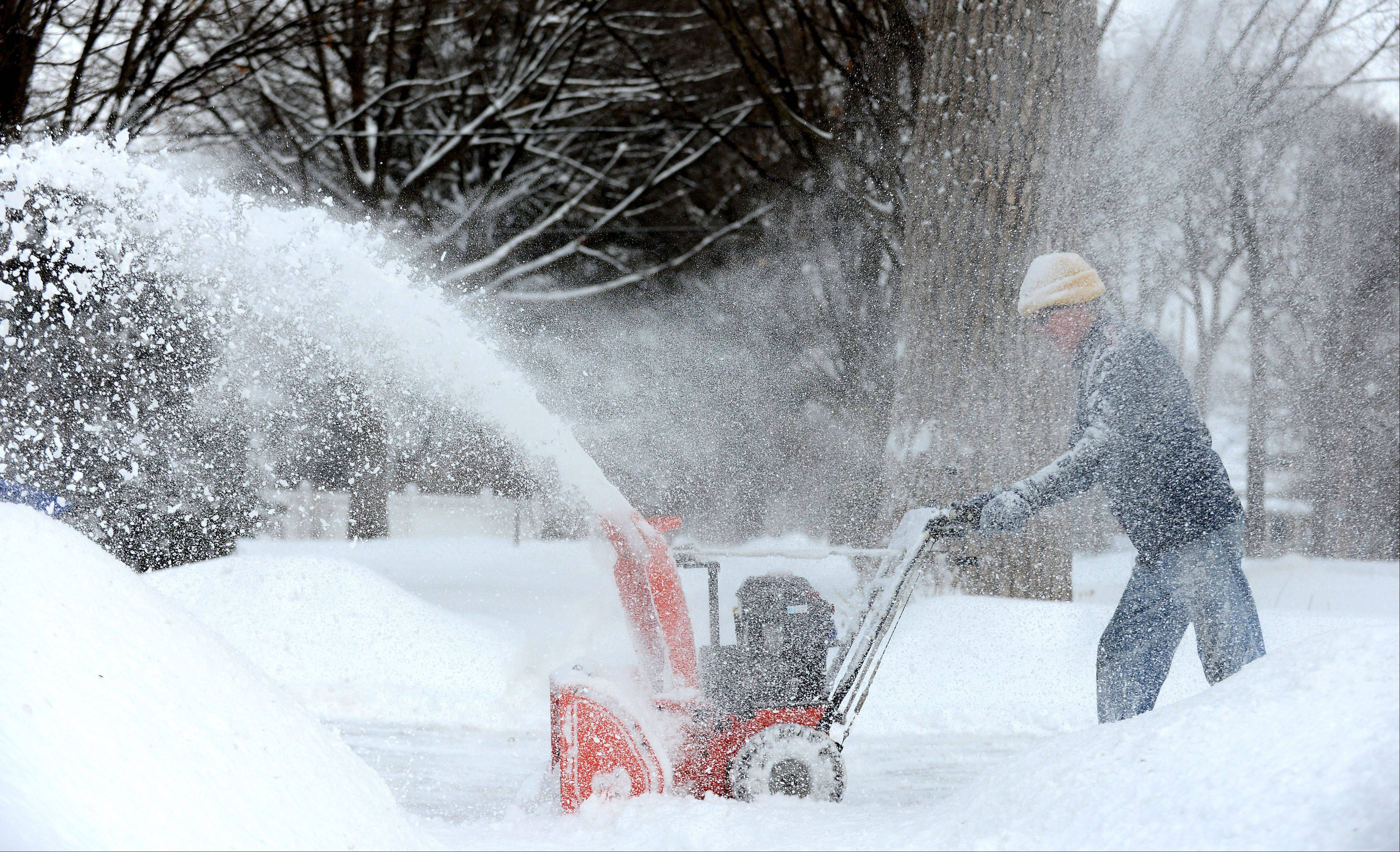 "John Gerlach blows snow at a neighbors house with friend Bob Rogers (not pictured) in Geneva Wednesday morning. ""We do the neighborhood,"" he said. ""We're both retired and we love being outdoors."" ""We're getting a little bit old, but what the heck. Our wives look out the windows every 10 minutes to see if we're still upright,"" he said."