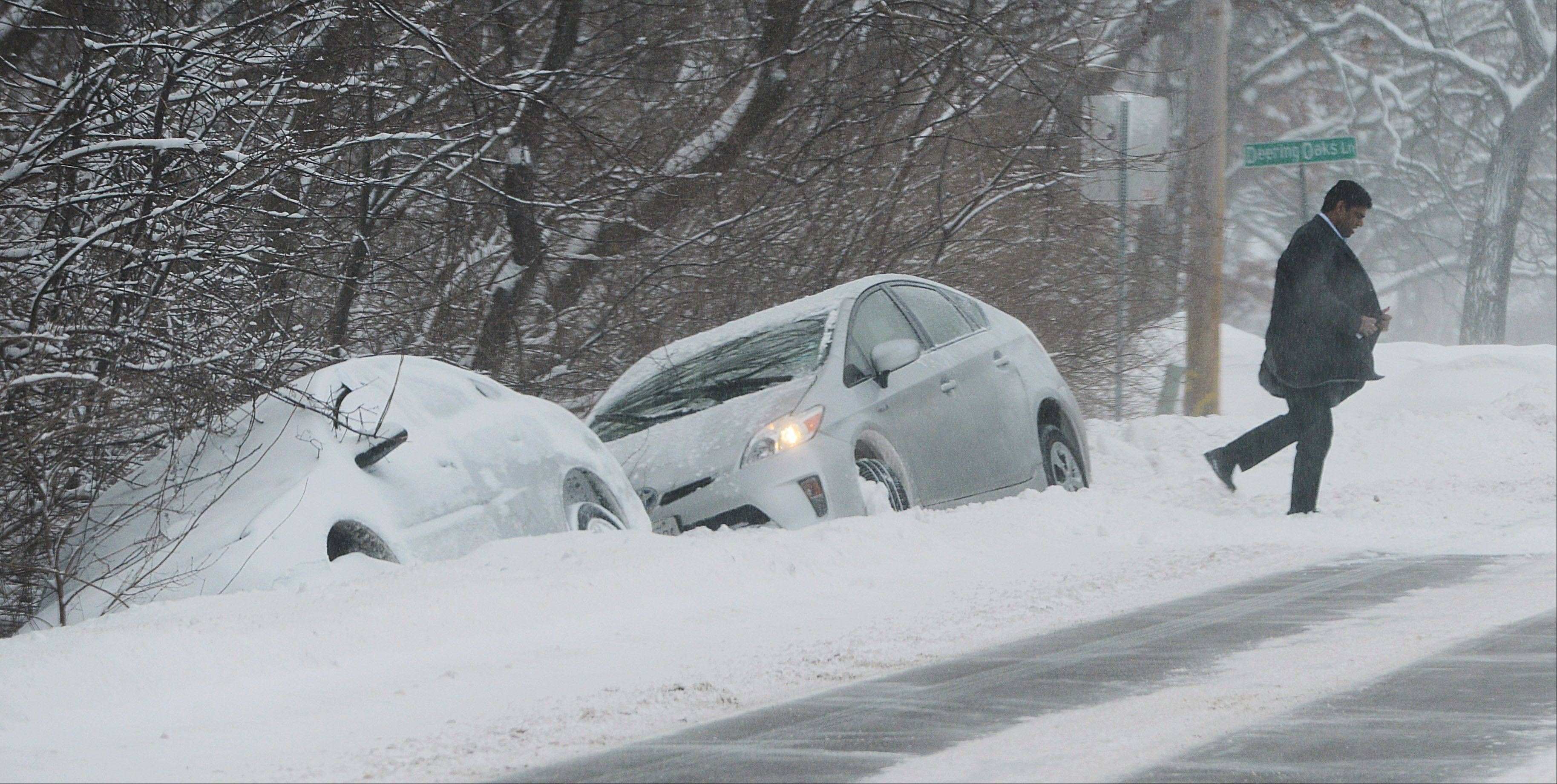 A driver emerges from his car after sliding into a ditch along Terra Cotta Road in Crystal Lake Wednesday morning. Another car sits in the same spot from an earlier incident.