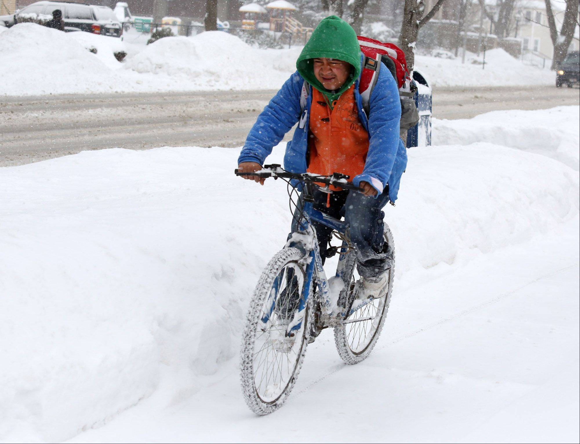 Gustavo Ernandes rides his bicycle to work on Lee Street in Des Plaines on Thursday.