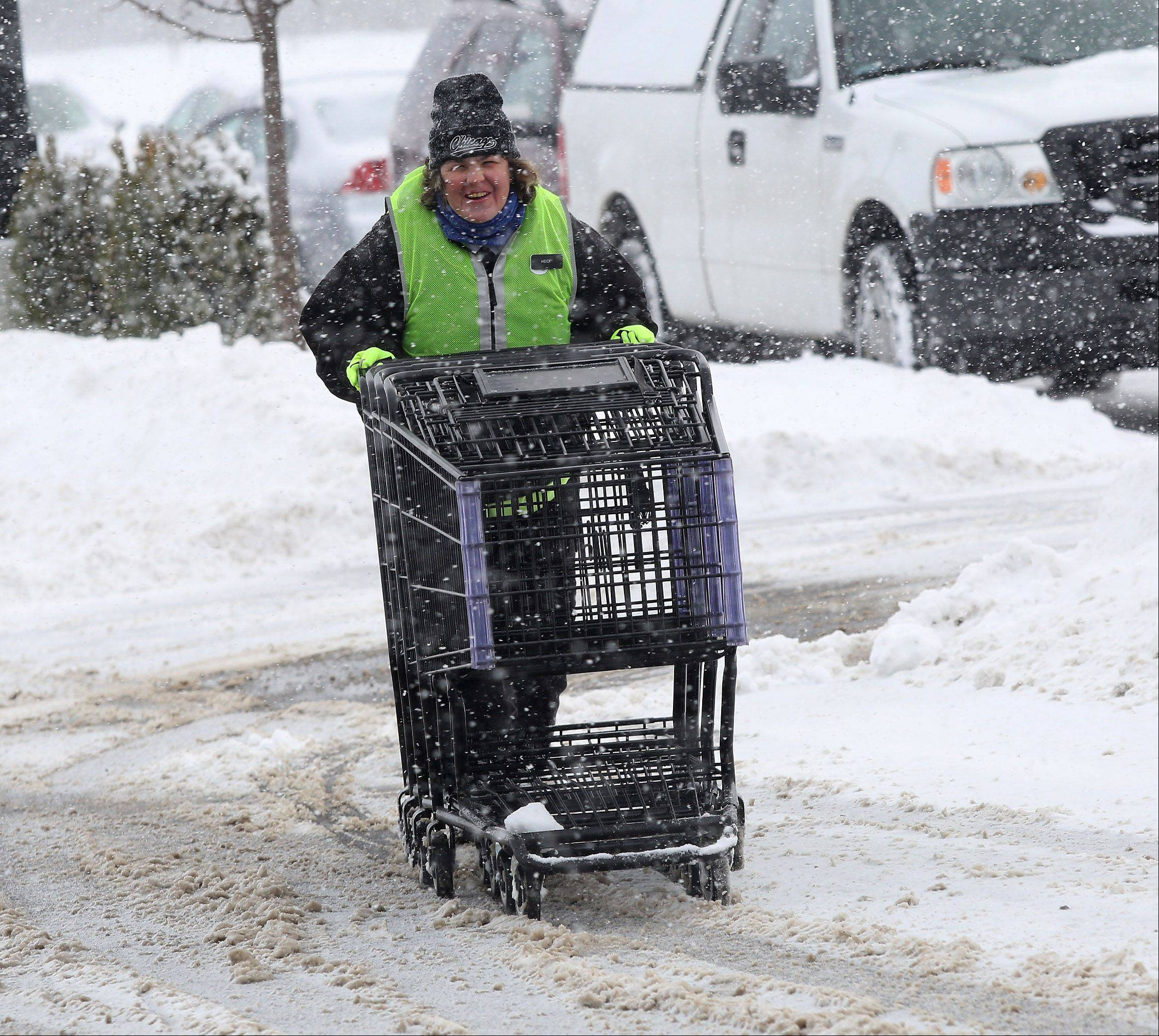 Mariano's grocery store employee Heidi Snodie pushes carts in the snow at the new store in Lake Zurich on Wednesday. The overnight snowstorm forced area residents to once again dig out their driveways and face morning traffic problems on commutes to work and school.