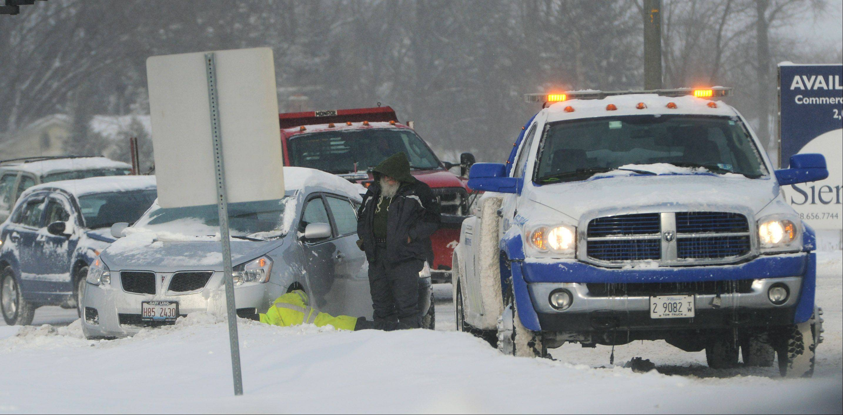 A driver waits to have his car pulled out from a snowbank along Route 176 in Island Lake. Wednesday morning's commute was hampered by overnight snowfall.