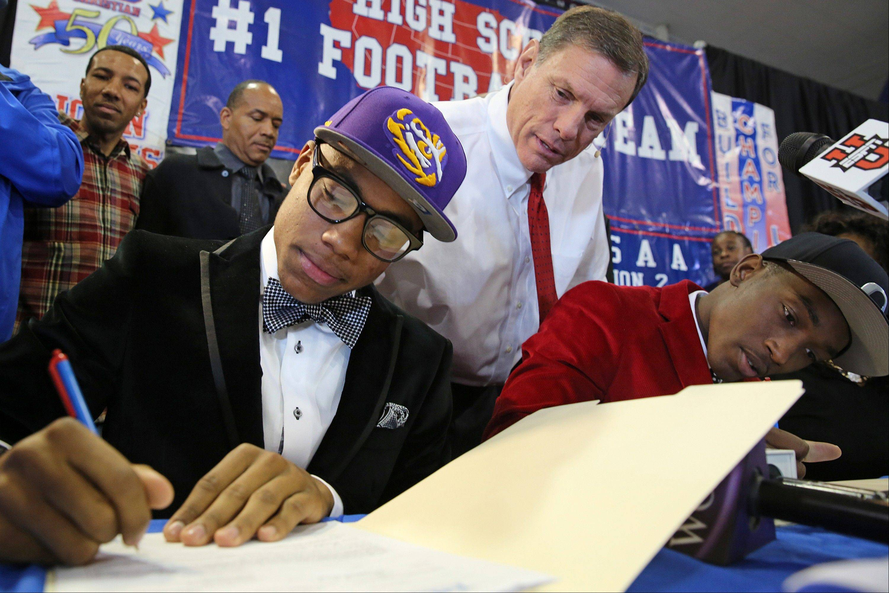 John Curtis High School football coach J.T. Curtis watches as Malachi Dupre signs his letter of intent for LSU in the high school's gym on Wednesday's National Signing Day.