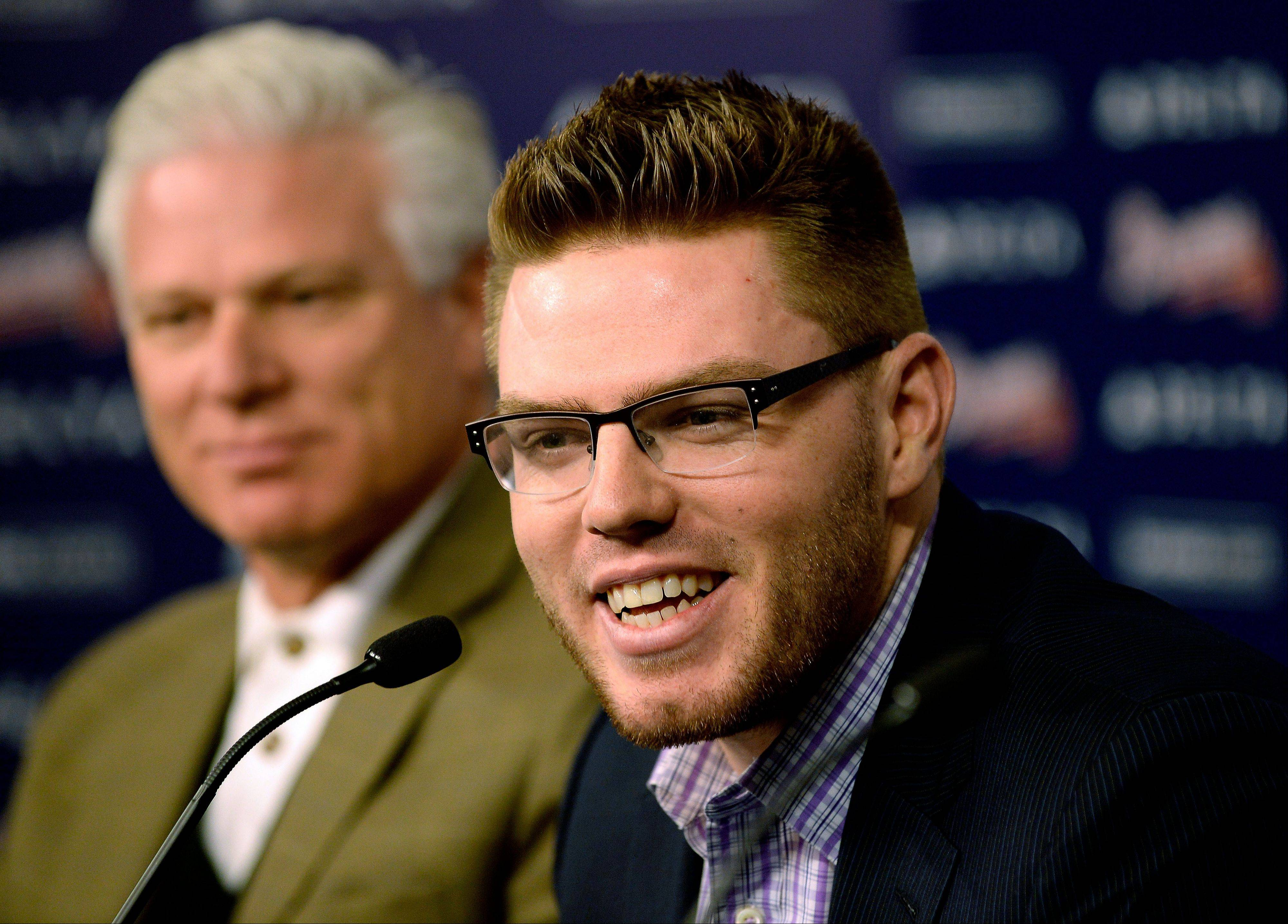Atlanta Braves first baseman Freddie Freeman sits next to manager Frank Wren while discussing his new deal with the baseball team, Wednesday, Feb. 5, 2014, in Atlanta. Freeman said Wednesday his $135 million, eight-year deal shows he should simply continue on his current path to becoming one of the best first basemen. (AP Photo/Atlanta Journal-Constitution, David Tulis) GWINNETT OUT MARIETTA OUT LOCAL TV OUT (WXIA, WGCL, FOX 5)