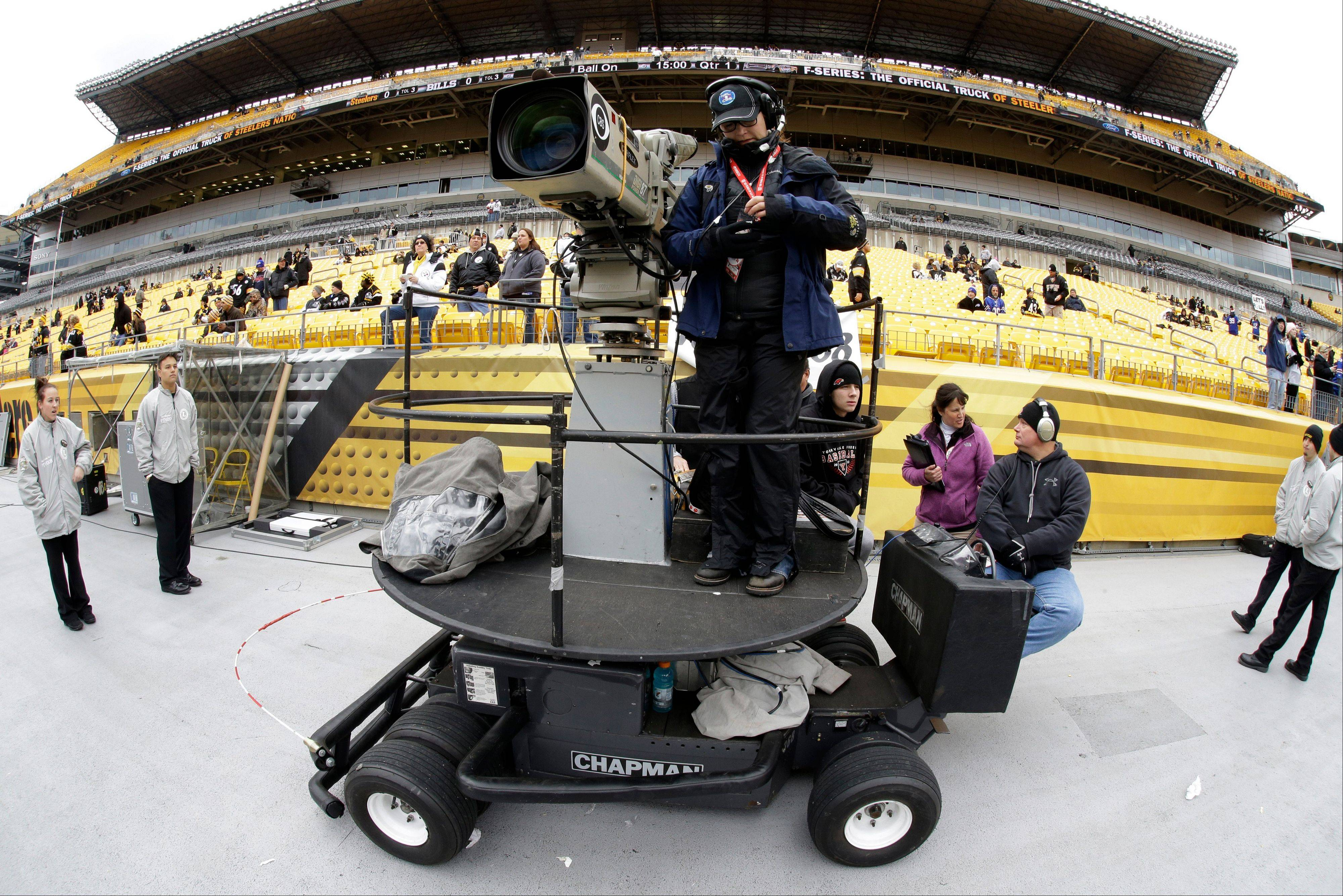 FILE - In this Nov. 10, 2013, file phot, a CBS sideline camera operator prepares for an NFL football game between the Pittsburgh Steelers and the Buffalo Bills in Pittsburgh. The NFL says CBS will televise eight of its Thursday night games next season. The leagues says the contract is for one year, and they have an option to extend it for 2015.