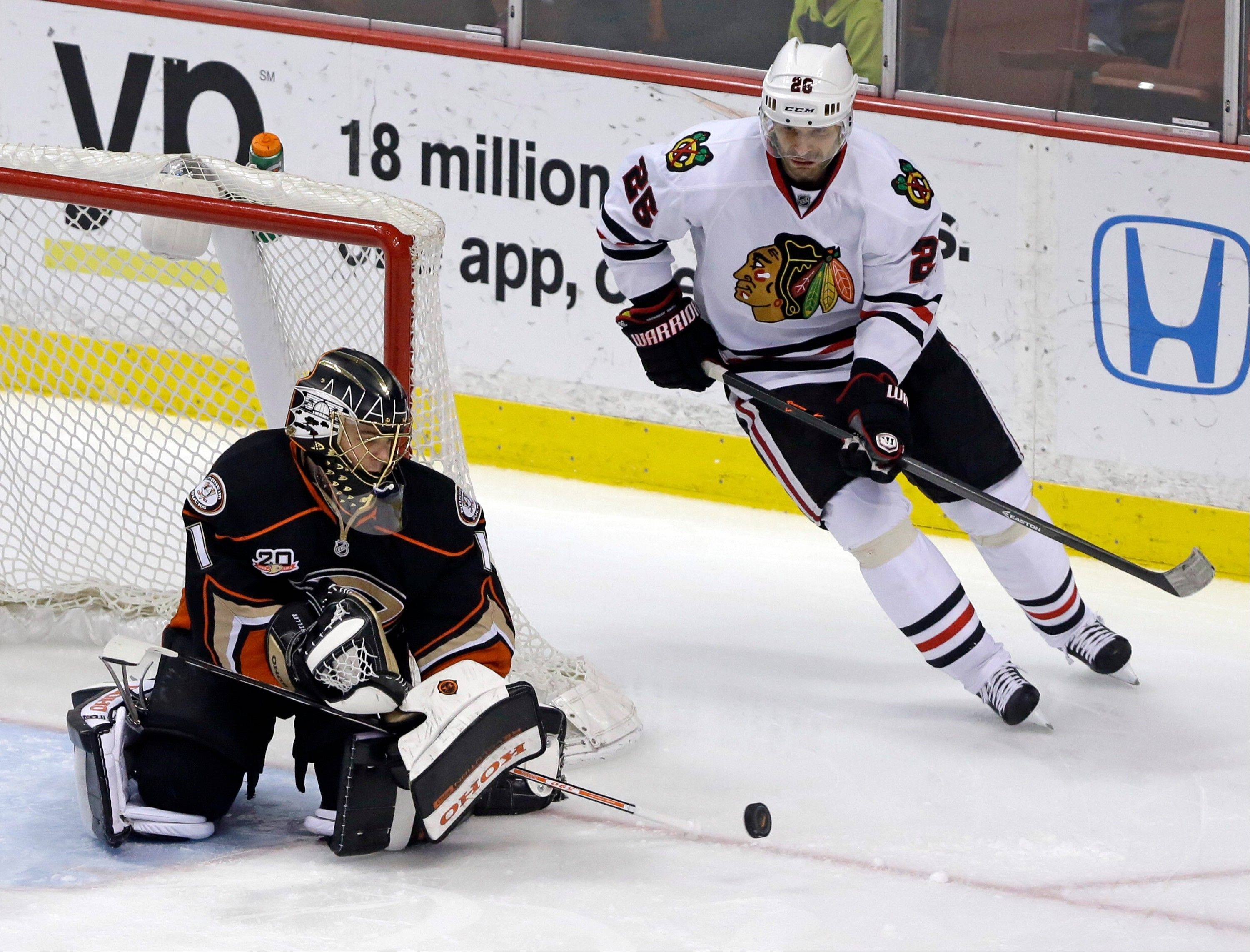 Anaheim Ducks goalie Jonas Hiller (1), of Switzerland, deflects the puck as Chicago Blackhawks center Michal Handzus (26), of the Czech Republic, skates past during the second period of an NHL hockey game in Anaheim, Calif., Wednesday, Feb. 5, 2014.