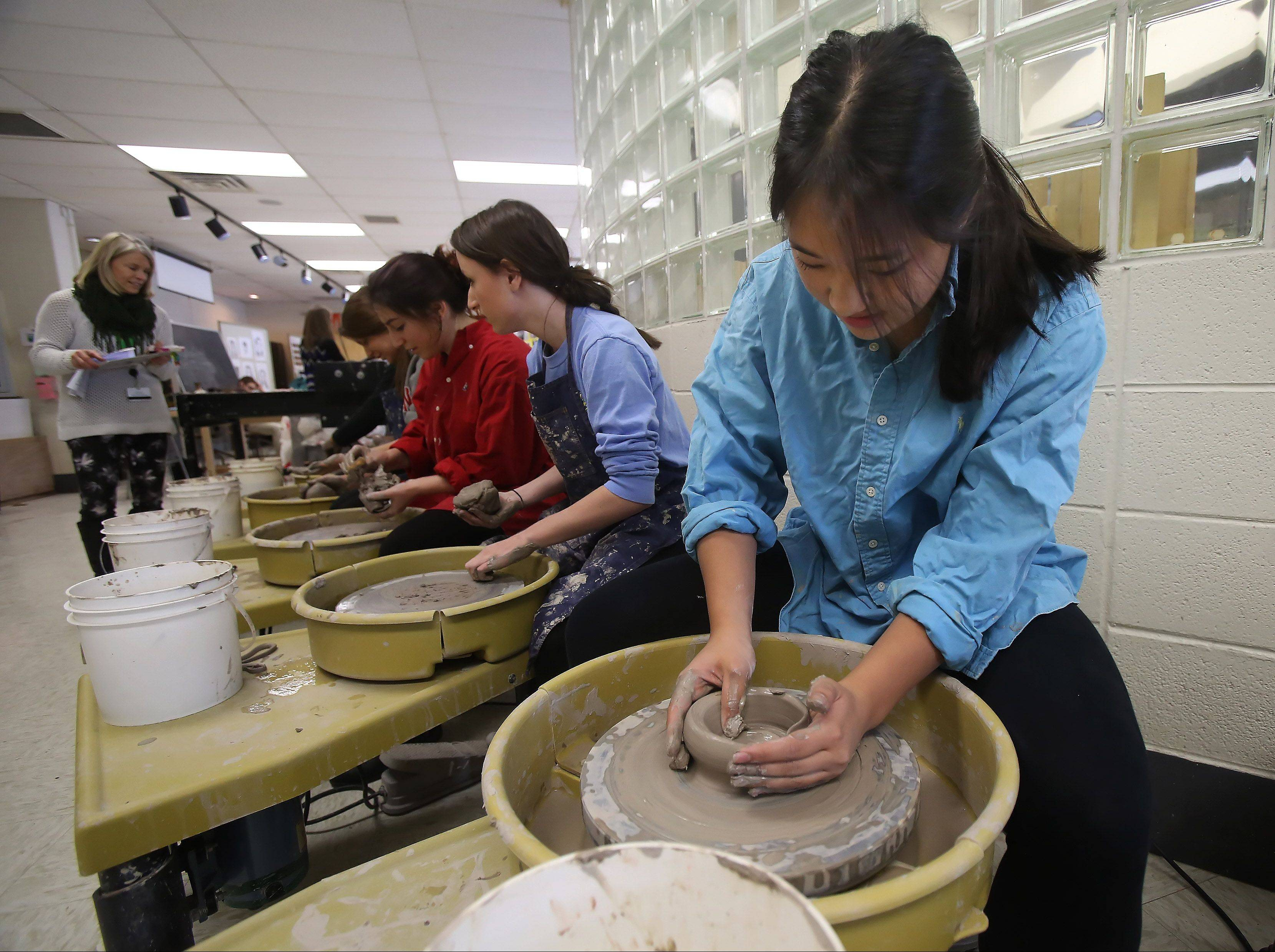 Senior Stephanie Wang, right, learns to throw a clay pot during the 10th Odyssey fine arts festival Wednesday at Stevenson High School in Lincolnshire. The two-day event featured musical and stage performances and student participation in art media, dancing, music and literature arts.