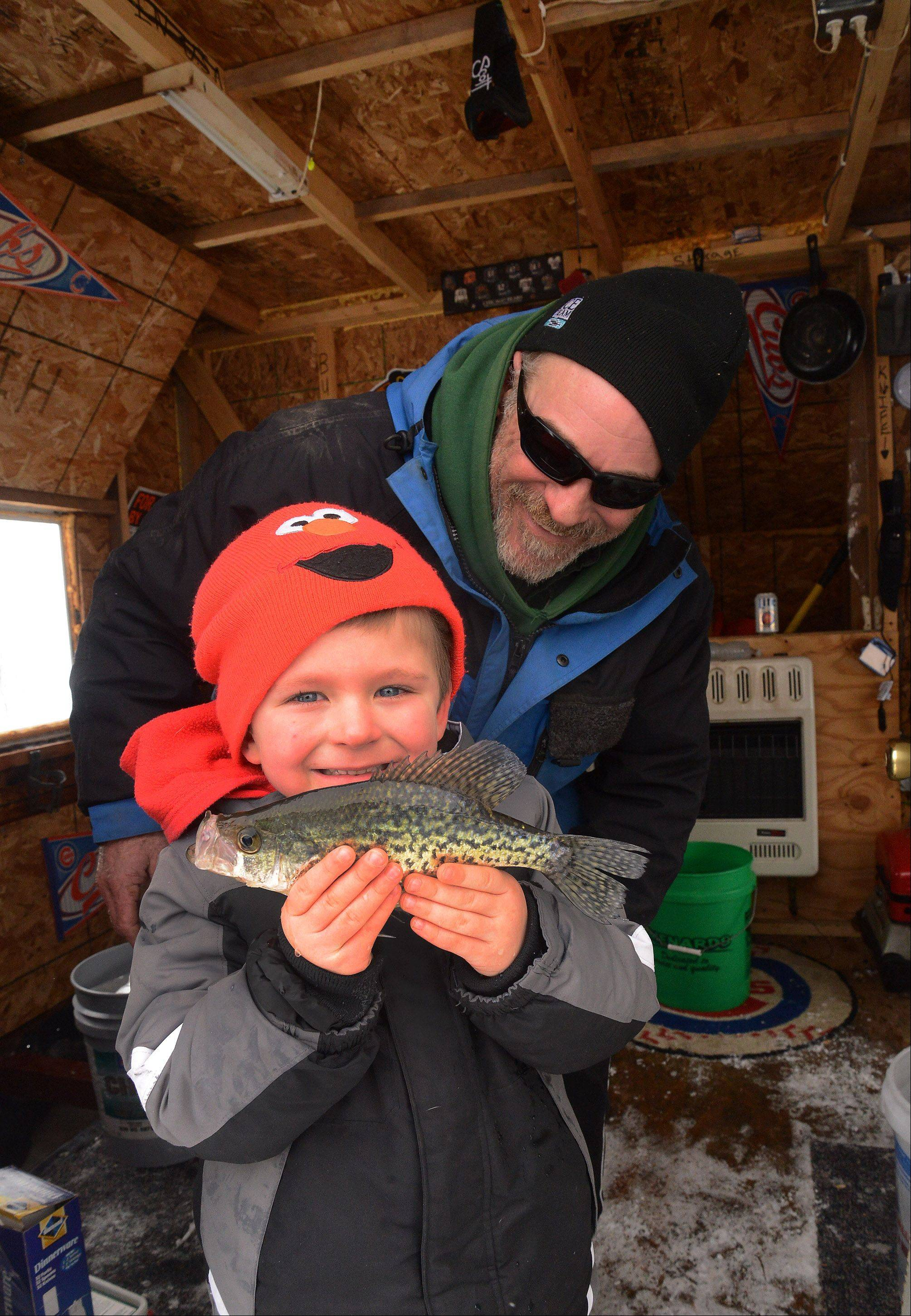 Devan Marcomb, 5, holds up a crappie he caught with his uncle Bob Kiesgen, both from Antioch, Saturday at the 54th Annual Chain O� Lakes Fishing Derby at the Thirsty Turtle in Antioch.