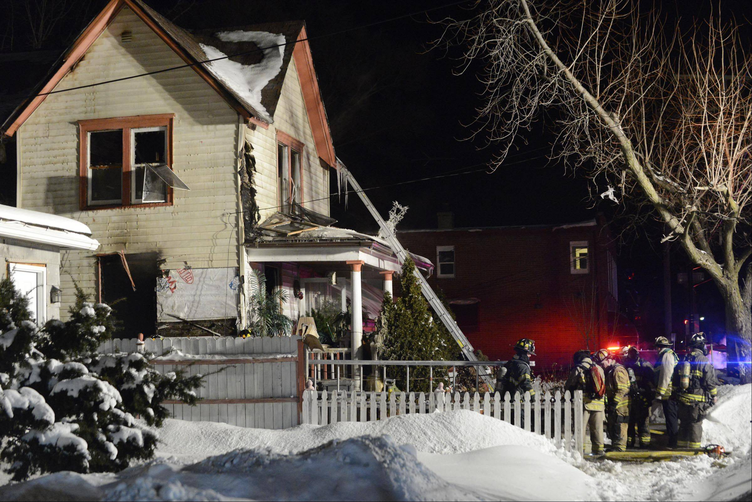 Firefighters work at the scene of a house fire Thursday night near the intersection of Route 25 and Villa Street in Elgin.