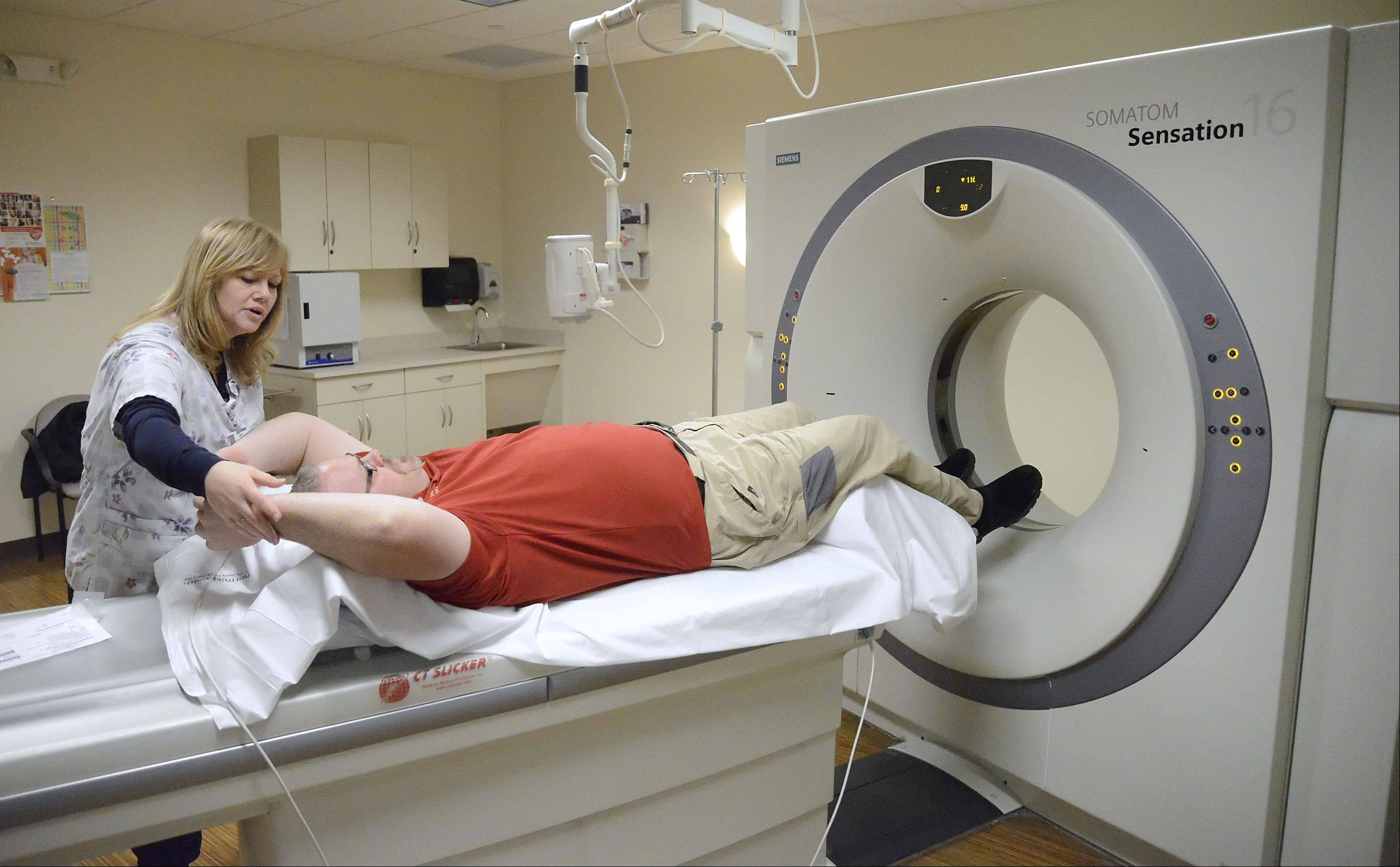 "Laura Stoecker/lstoecker@dailyherald.com Registered CT Technologist, Kat Kearney, has Kane County Coroner Rob Russell raises his arms above his head in prep for a heart CT scan during his ""Heart & Vascular Risk Screening Package"" at the Advocate Sherman Outpatient Center in South Elgin on Thursday, January 30. Russell was in the scanner less than 30 seconds."