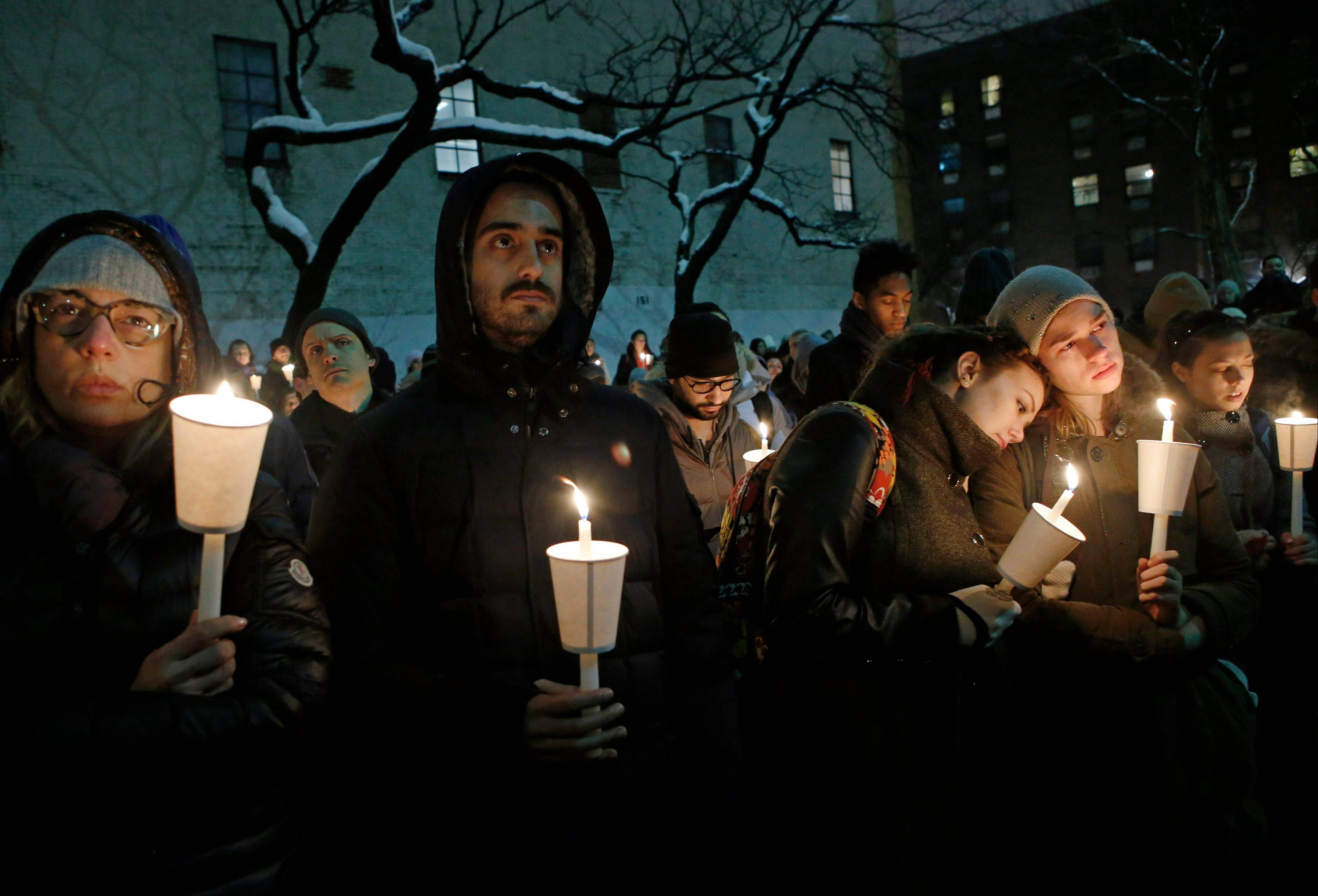 People listen to actor Eric Bogosian speak during a candlelight vigil for actor Philip Seymour Hoffman at the Bank Street Theater, home of the Labyrinth Theater Company, Wednesday, Feb. 5, 2014, in New York. Hoffman died Sunday of a suspected drug overdose.