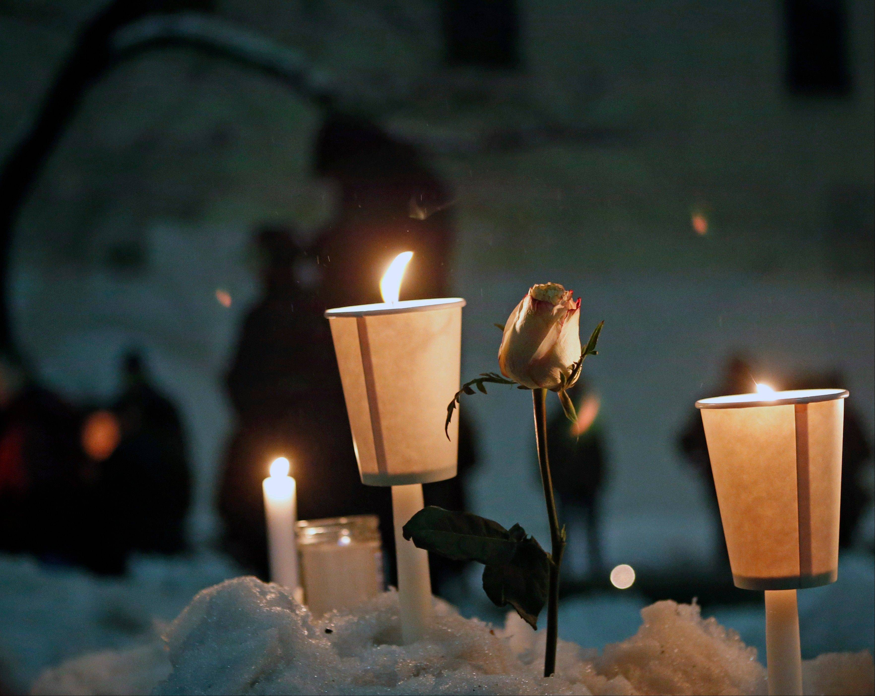 Candles burn alongside a rose left in a snowbank following a candlelight vigil sponsored by the Labyrinth Theater Company in the courtyard of the Bank Street theater for actor Philip Seymour Hoffman, a company member and former Labyrinth artistic director, Wednesday, Feb. 5, 2014, in New York. Hoffman died on Sunday of a suspected drug overdose.