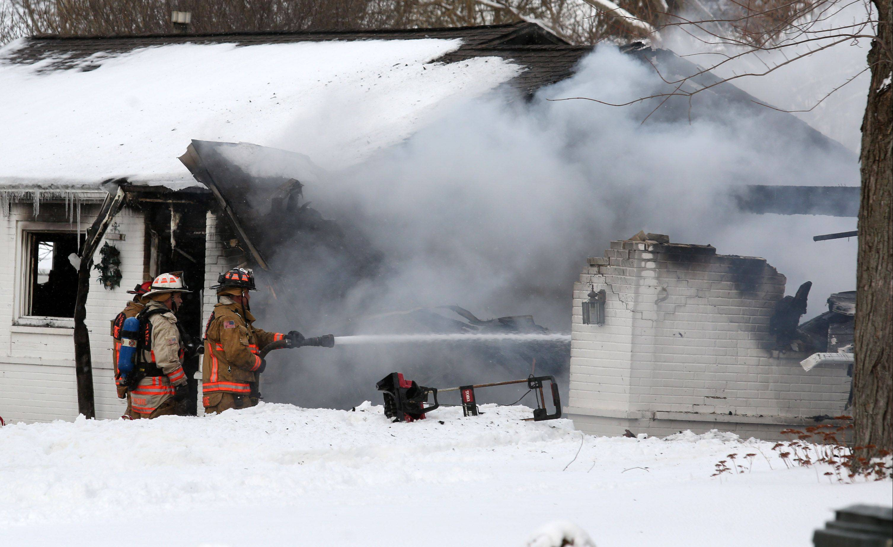 A Hoffman Estates firefighter sprays water on a house fire on Basswood Street between Golf and Higgins roads Wednesday in Hoffman Estates. Fire investigators are searching for the cause of the fire, which left the home uninhabitable.